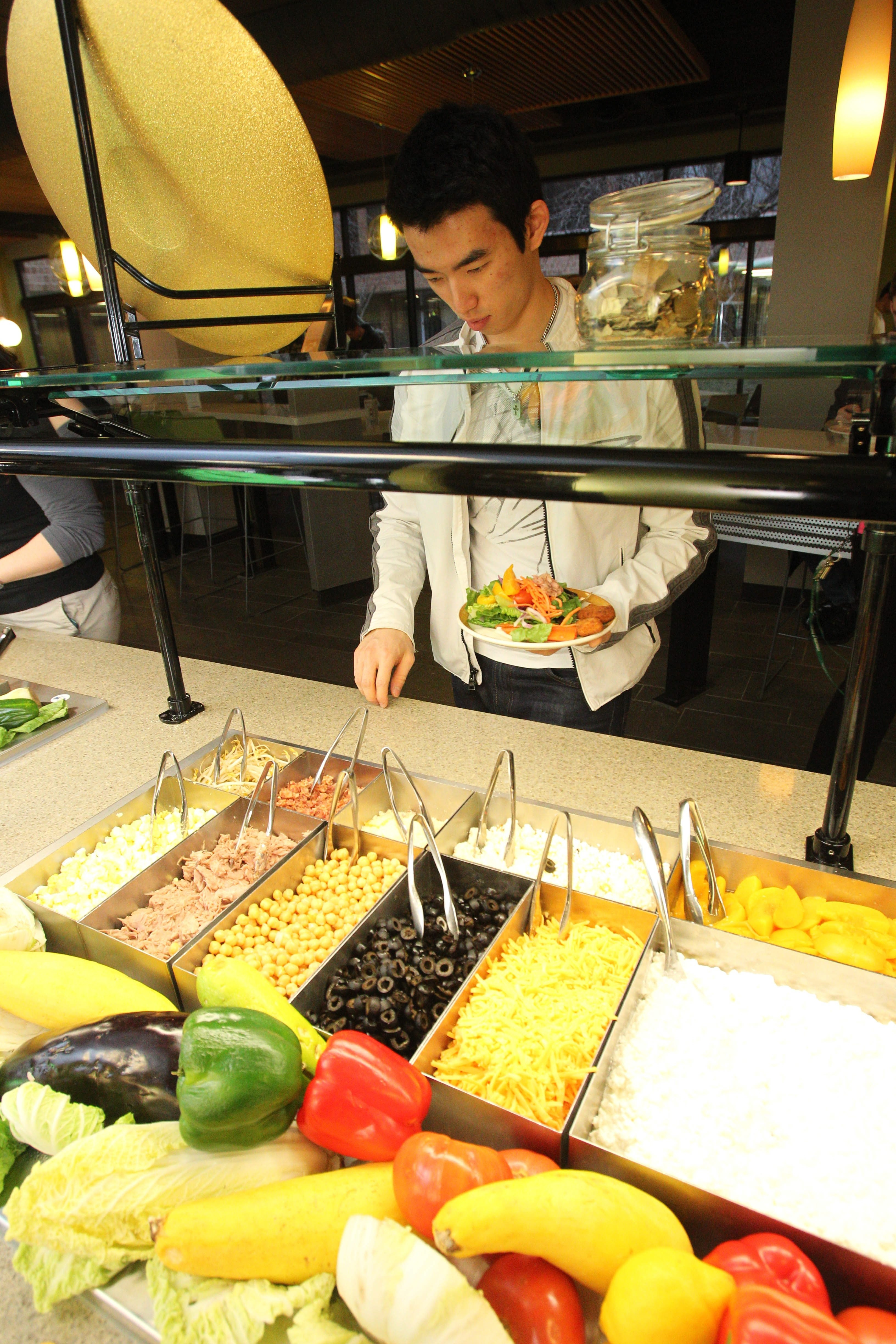 Food service at at the Red Jacket Quad in the Ellicott Complex at UB North campus had a huge makeover with a new look and an upscale menu.  Seokchan Swak fills his plate at the salad bar.   (Sharon Cantillon/Buffalo News)
