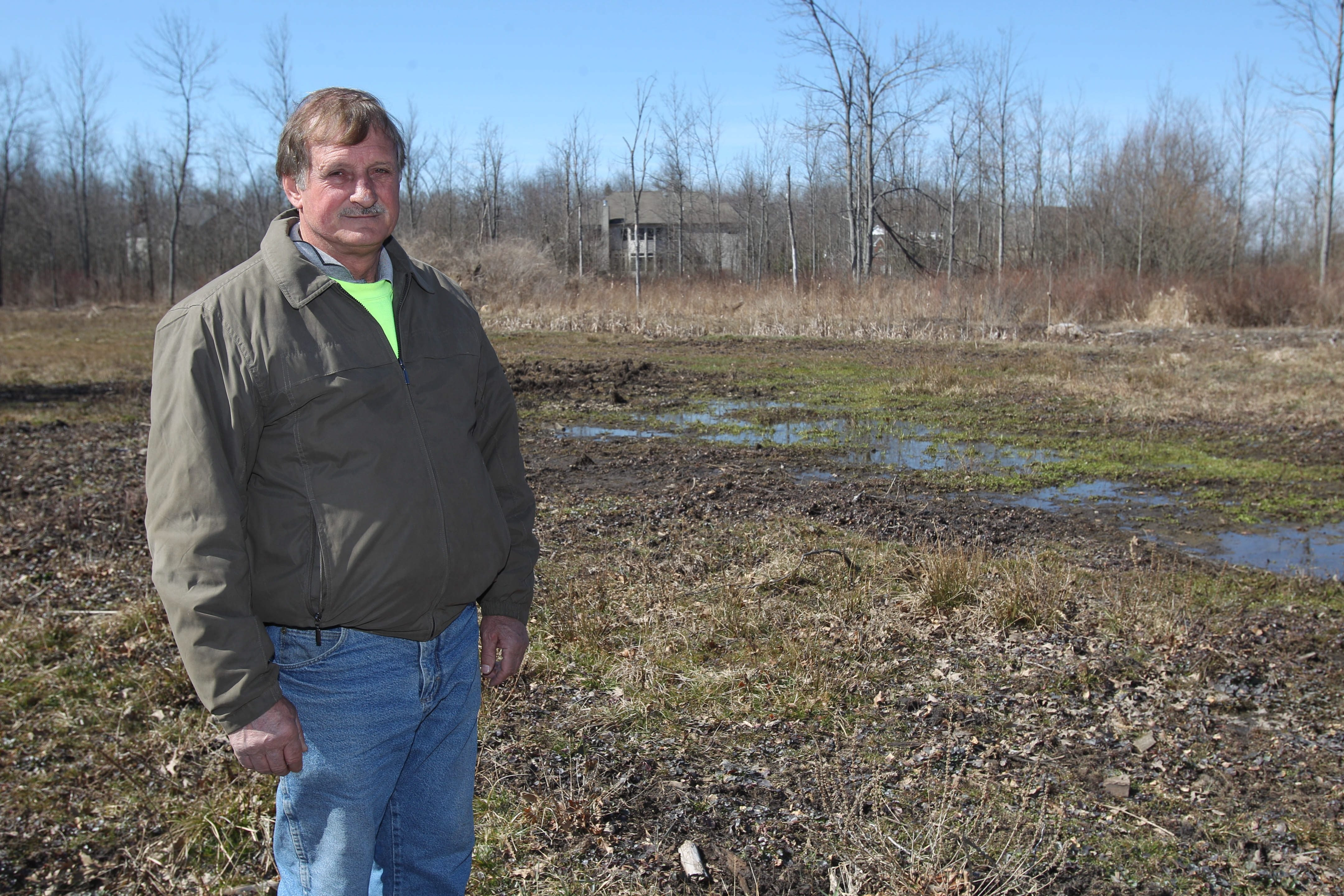 Paul Marinaccio won a $1.6 million verdict against the Town of Clarence for allowing a developer to drain storm water onto his property. At times his land was under three feet of water. The housing development that prompted the problem is in the background.