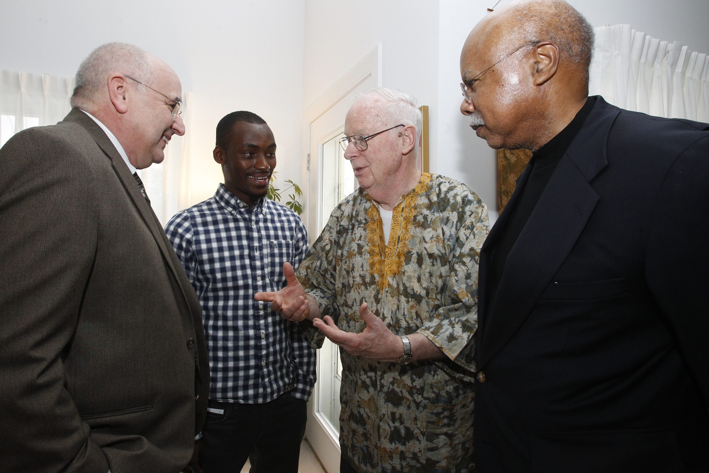 From left, James Johnson, UB student Sanusi Kamara, Reed Taylor and Willis Logan gather at a volunteer's Amherst home Saturday to discuss a 1969 project to build a hospital in Sierra Leone.