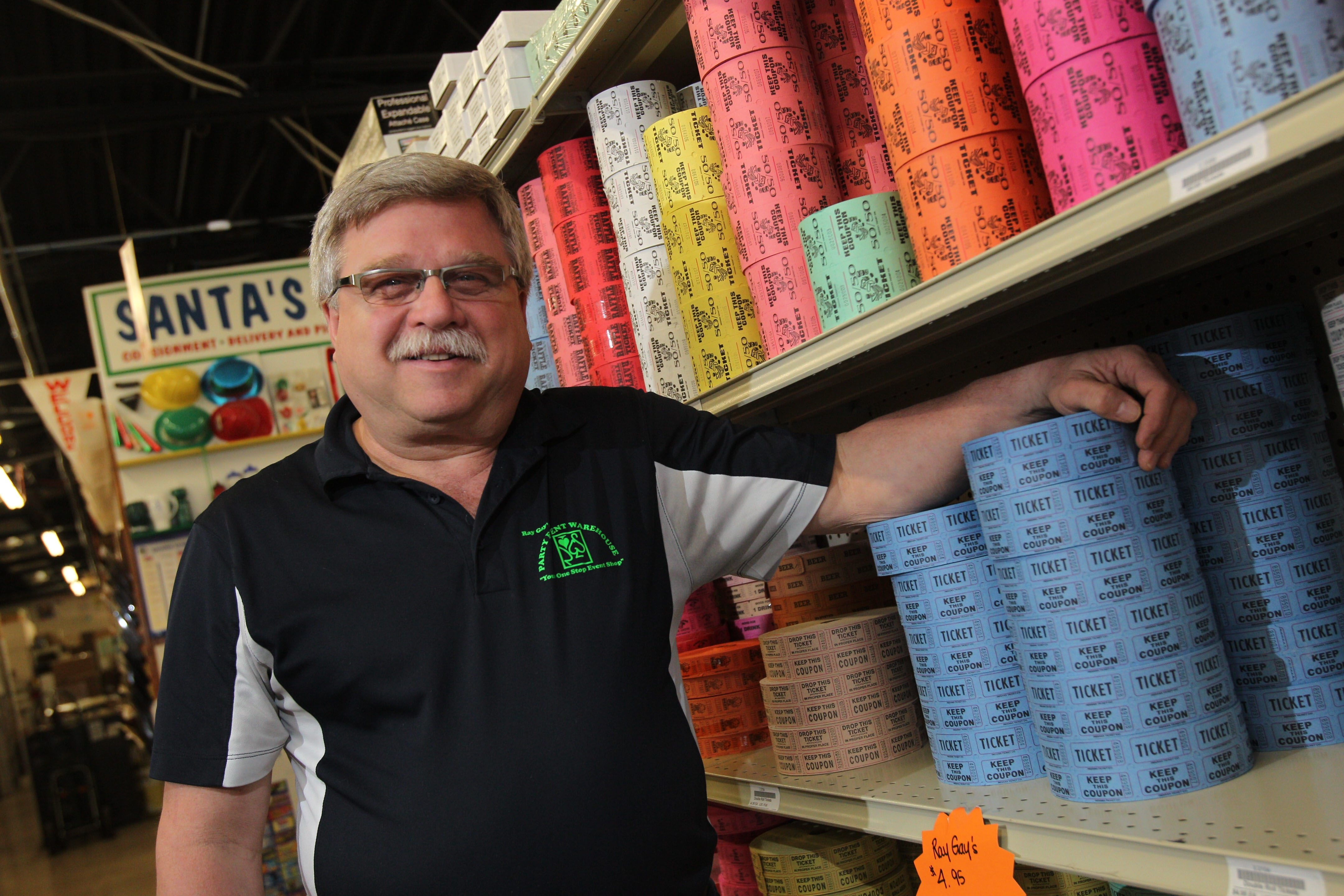 Ray Gay Sales in Cheektowaga supplies equipment and materials for fundraising events. Owner Chuck Gajewski stands near a shelf with thousands of fundraiser tickets.