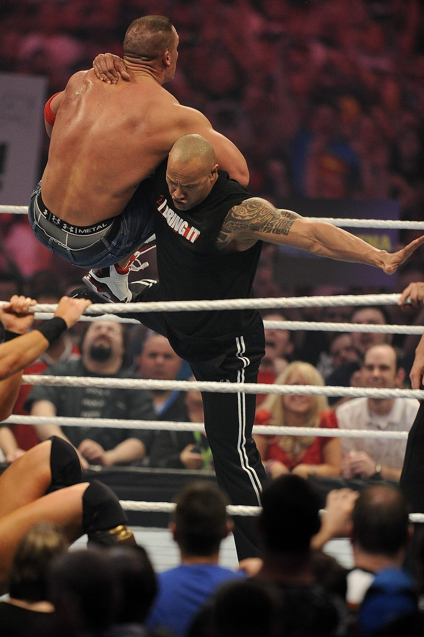 """Dwayne """"The Rock"""" Johnson, right, delivers a """"Rock Bottom"""" to John Cena at WrestleMania 27. The two renew hostilities Sunday at """"WrestleMania 29."""