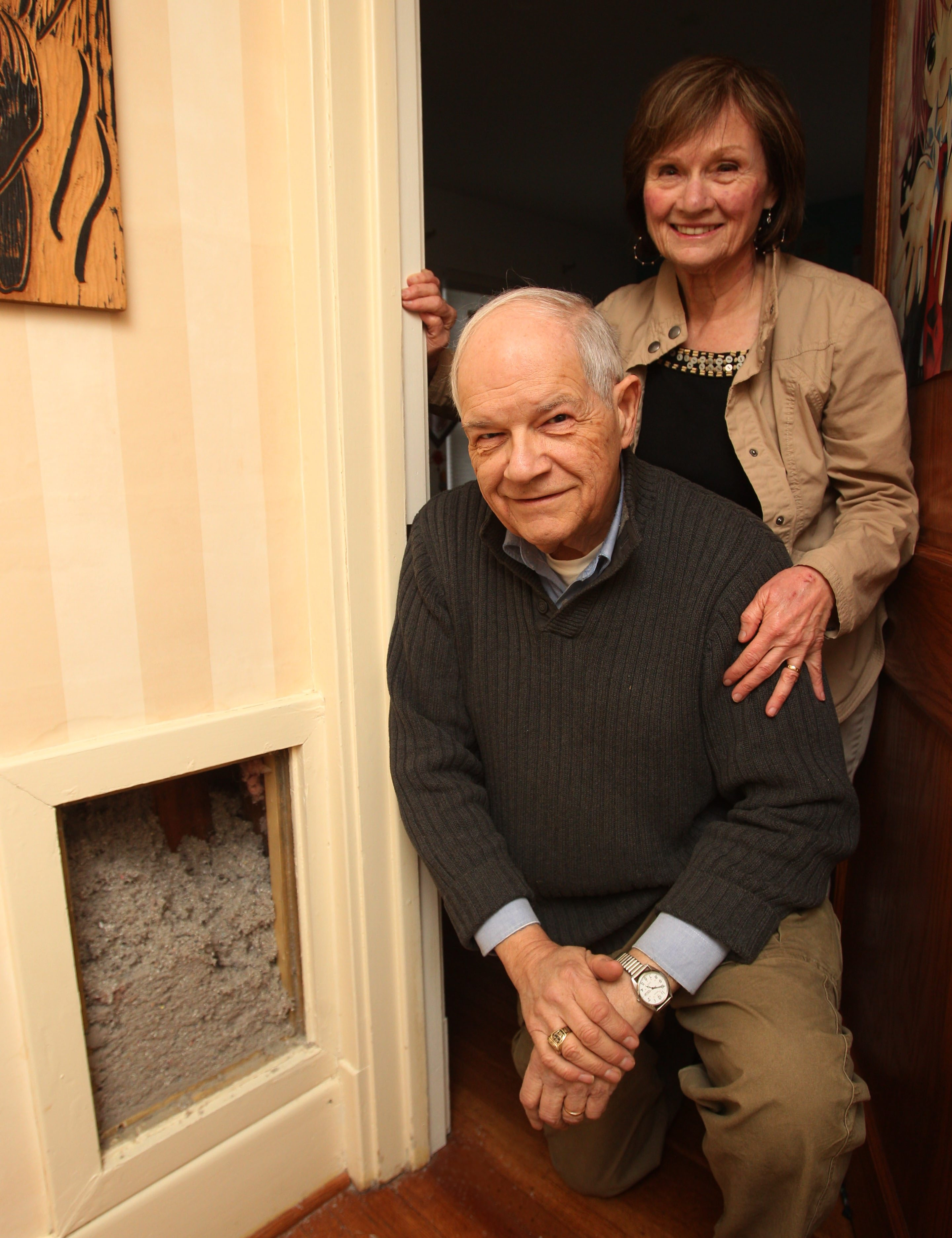Denis and Mary Uminski show off some of the wood cellulose insulation that was blown into the walls, second-floor ceiling and attic floor of their Kenmore home through a state program.