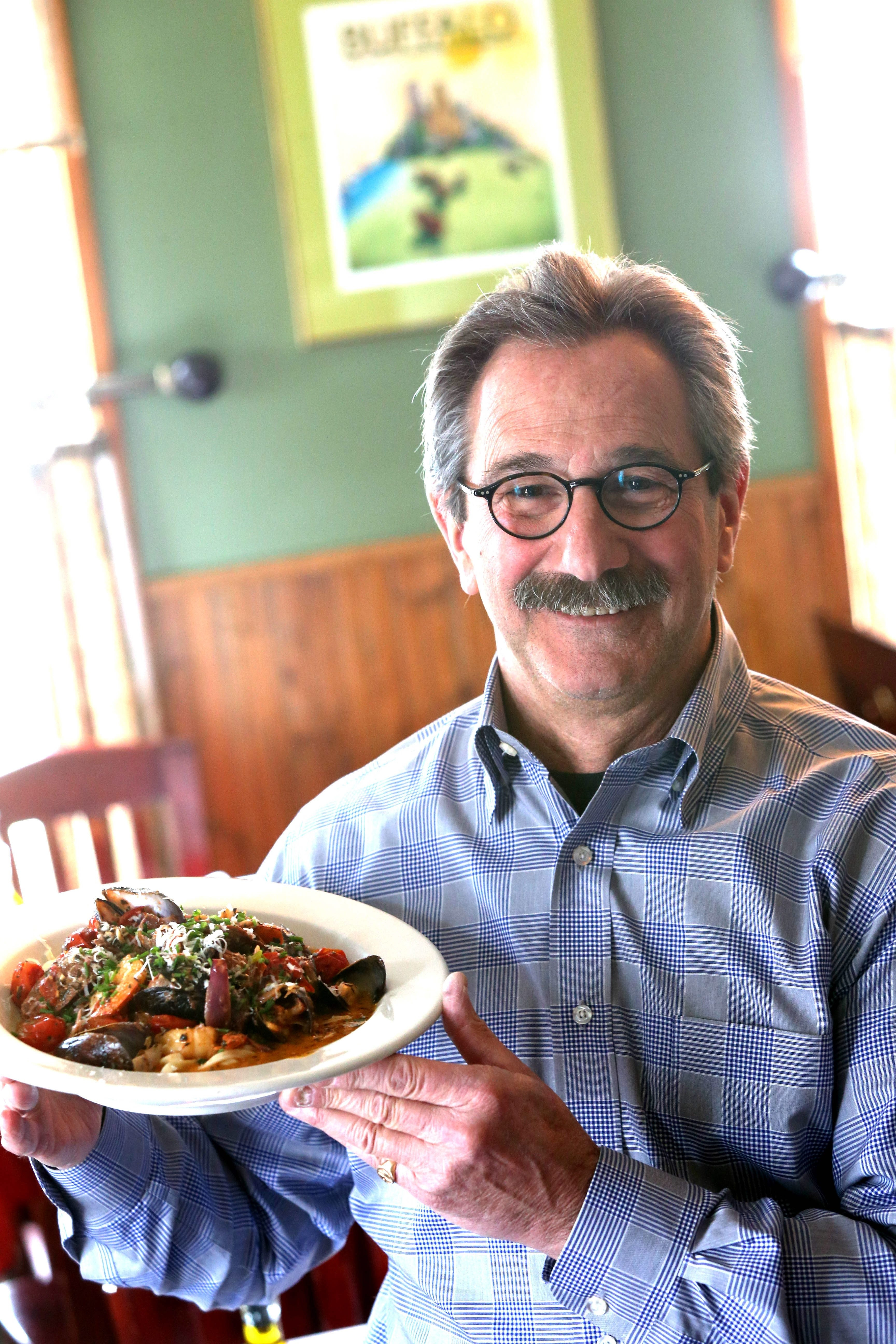 Lee Federiconi, owner of Lebro's in Getzville, shows off a plate of homemade pasta with sausage and seafood medley.