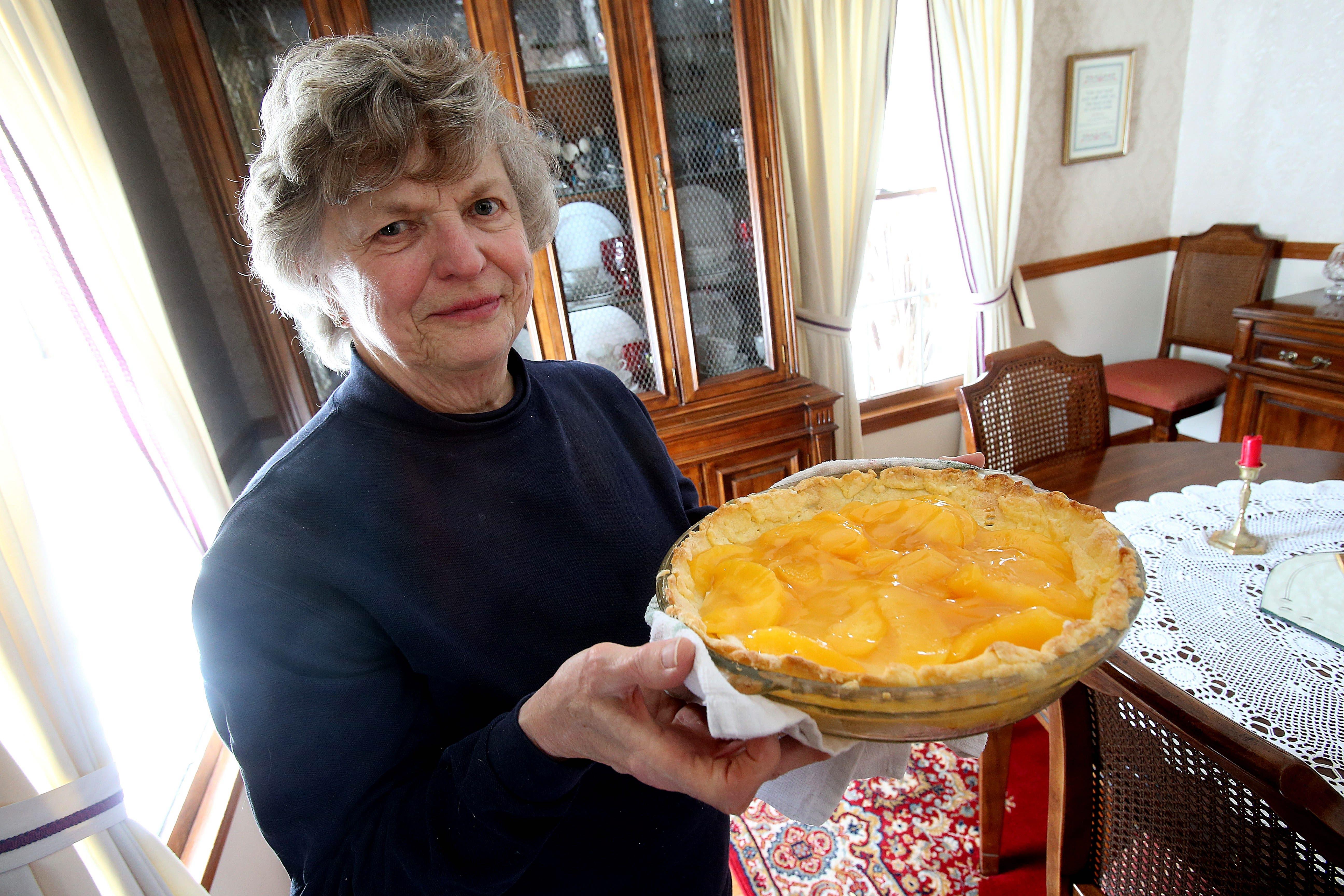 Joan Skop shows off her peach pie made with gluten-free crust.   (Robert Kirkham/Buffalo News)