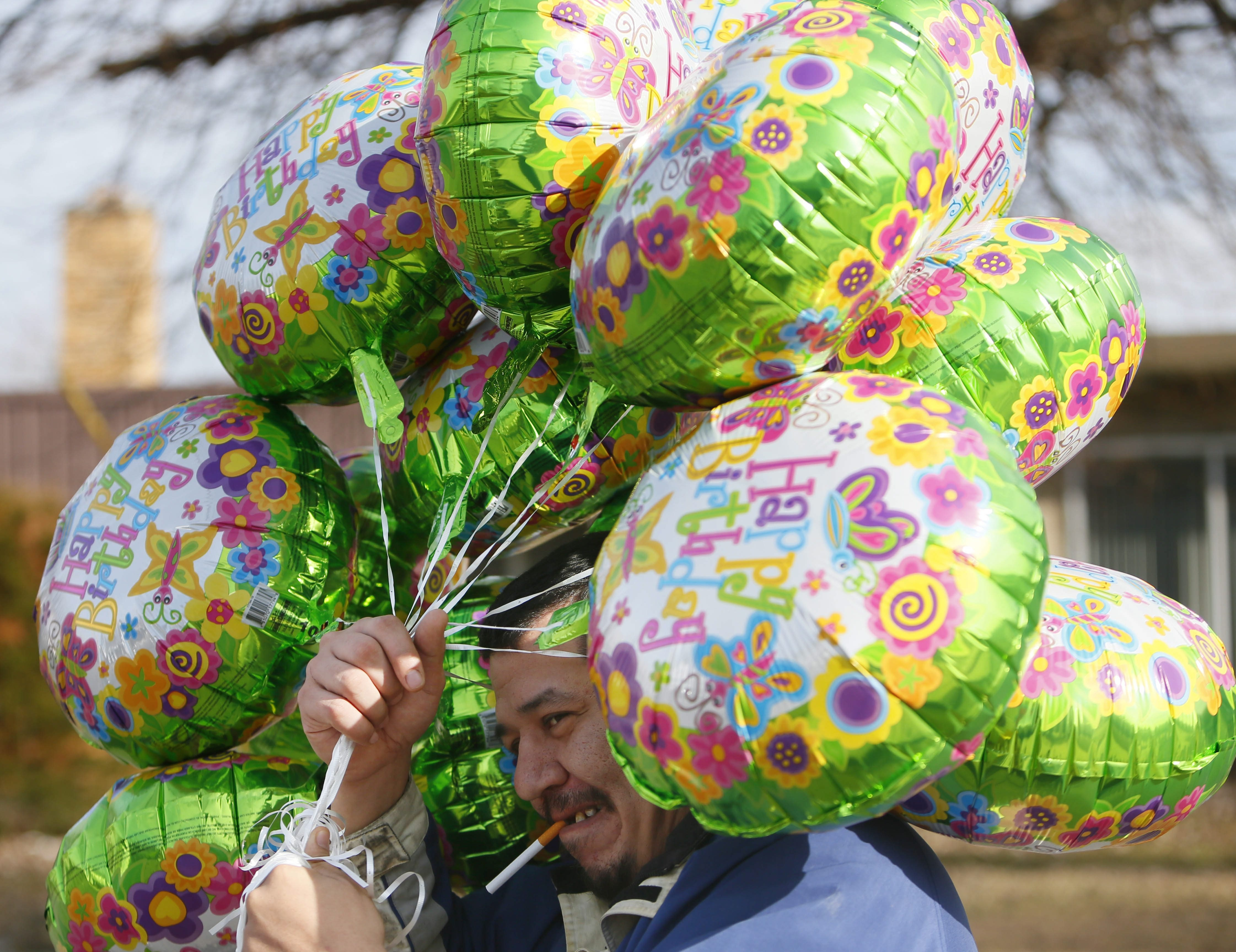Randall Reuben carries a bunch of balloons he bought for his daughter Maleeah's first birthday as he walks down Great Arrow Drive, Wednesday morning, March 27, 2013.  (Derek Gee/Buffalo News)