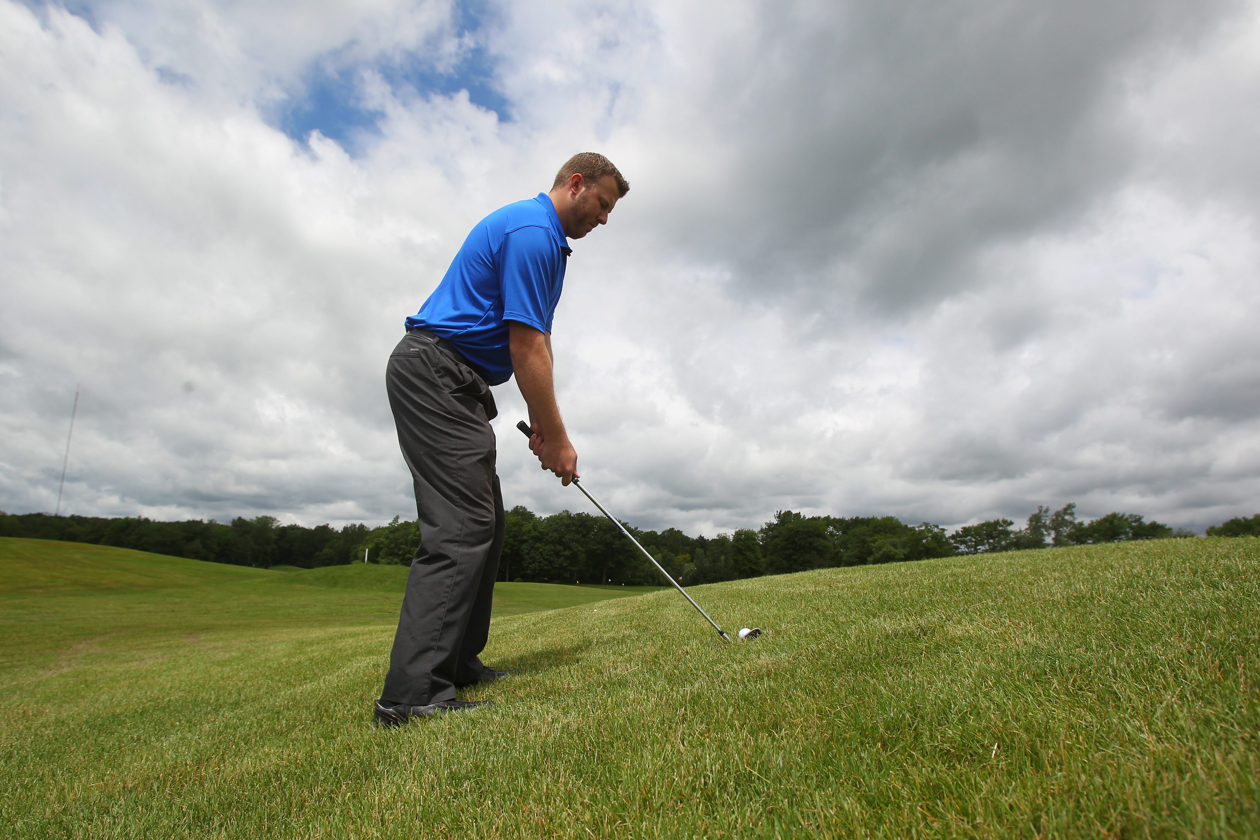 River Oaks Golf Club Head Professional Matt Clark demonstrates how to hit a side-hill lie at the club on Grand Island Tuesday.