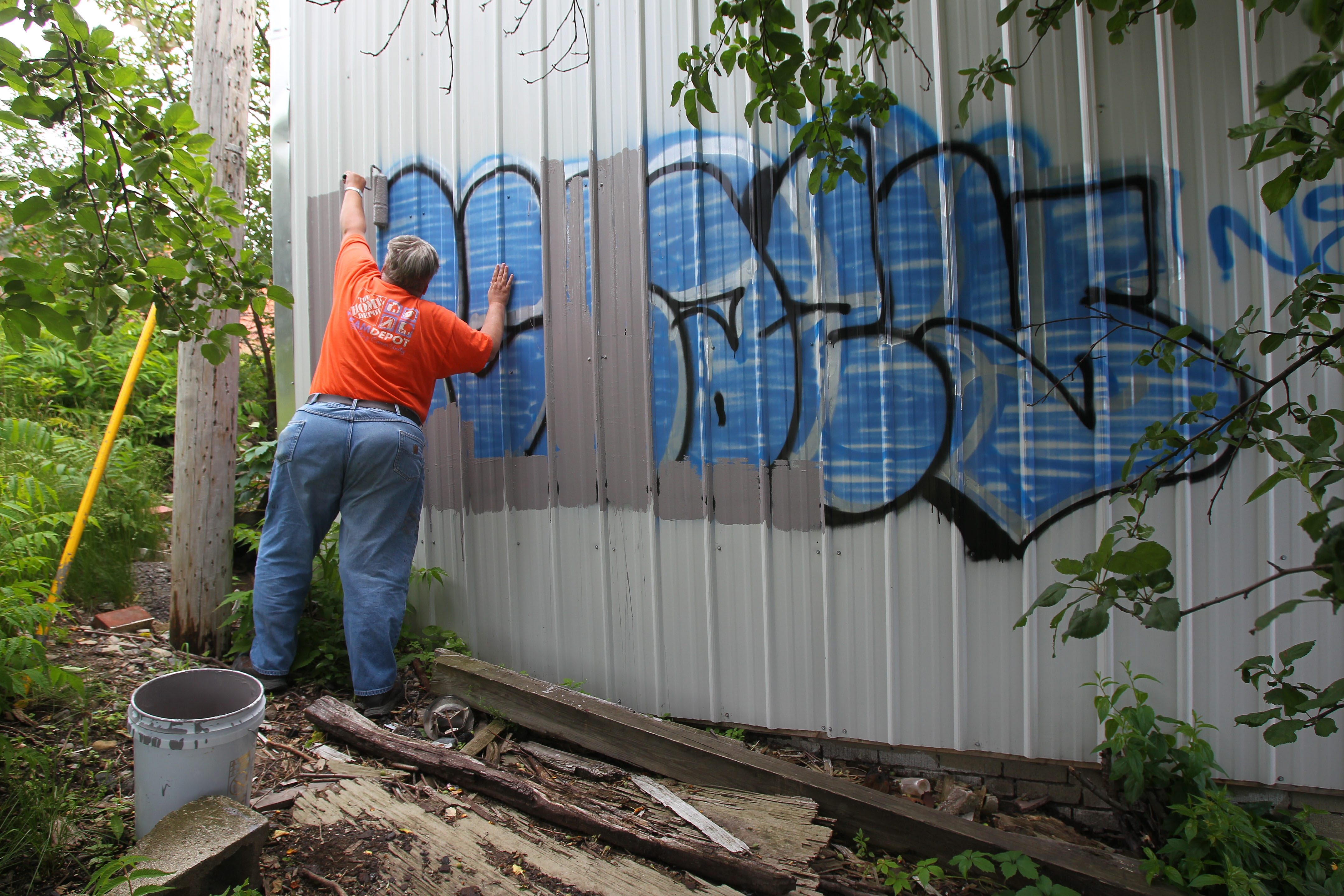 "Kevin Mathewson paints over graffiti on a building on Delaware Avenue in North Buffalo. Private property owners can be hit with fines for not removing graffiti, emblems of what Mayor Byron Brown has called ""a sense of lawlessness in the community."""
