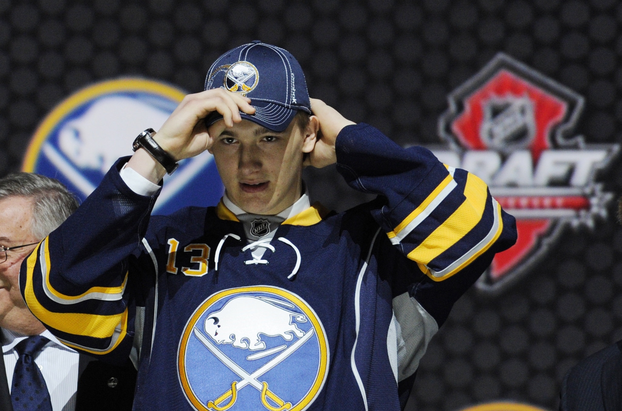 Nikita Zadorov, a defenseman, adjusts a Buffalo Sabres hat after being chosen 16th overall in the first round of the NHL draft.