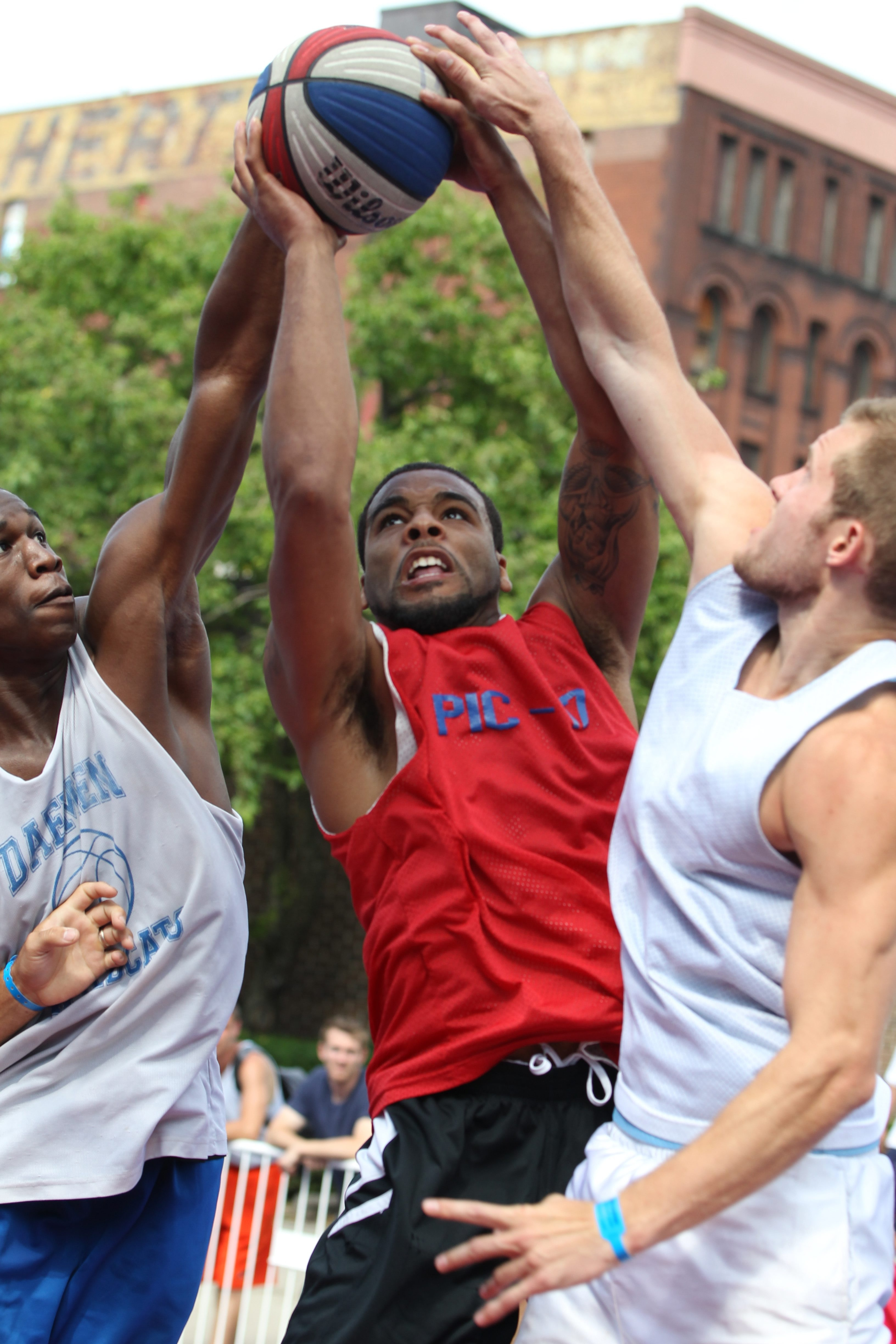 Jaysean Paige of Gerald's Barbershop scores over Nowak's Gerald Beverly and Troy Nowak in Sunday's title game.