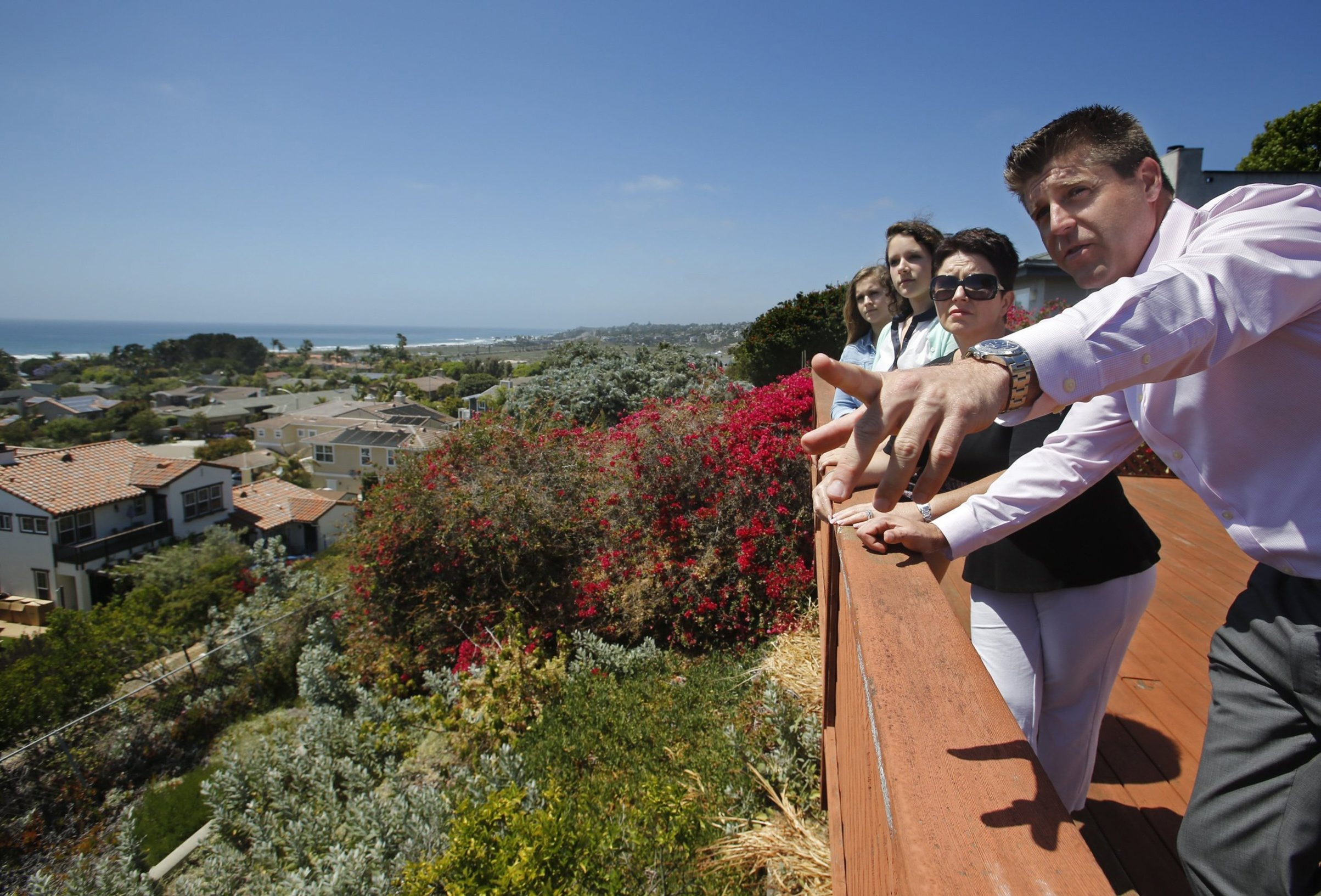 Realtor Ryan Mathys shows features to the Snyder family as they tour a home in Solana Beach, Calif. The family wanted a home on the beach but couldn't find one. Mathys searched social media and mailed homeowners until he found the property for sale before it hit any listing services.