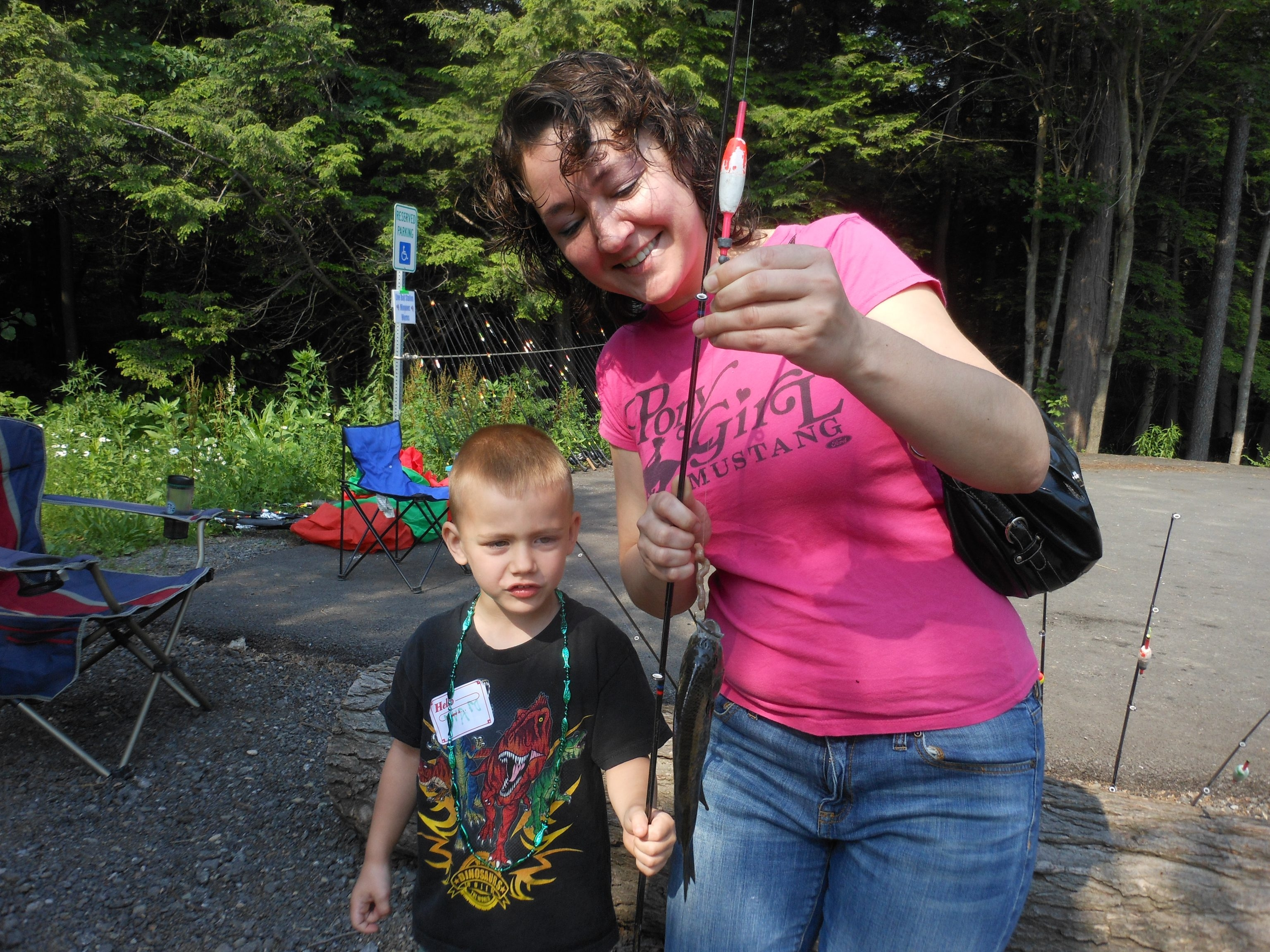 Edward Hajduk, age 4, of Buffalo shows his mom, Mary Hajduk, a big bluegill he caught at the start of a kids fishing day at Chestnut Ridge Park.