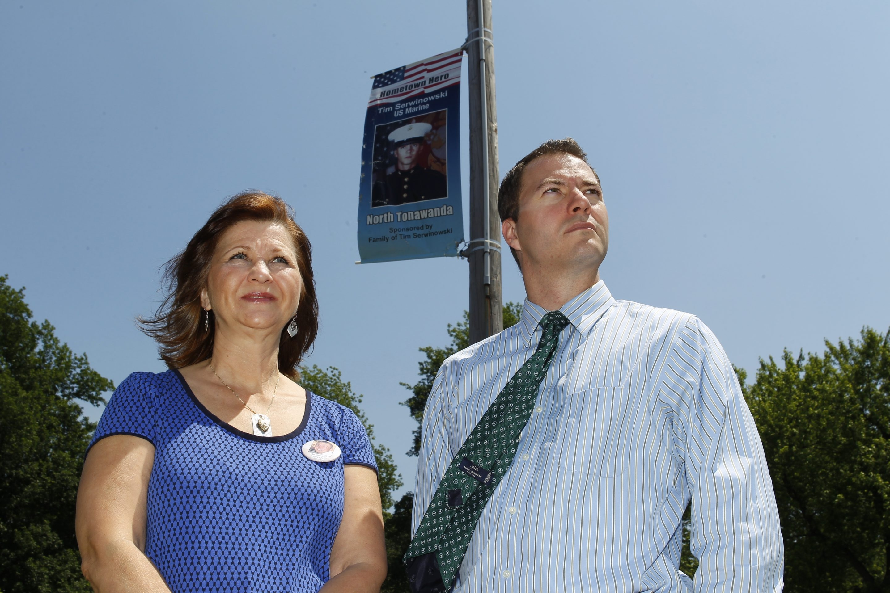 Sally Urban and North Tonawanda Mayor Robert G. Ortt  stand in front  of a banner honoring Urban's son outside City Hall.