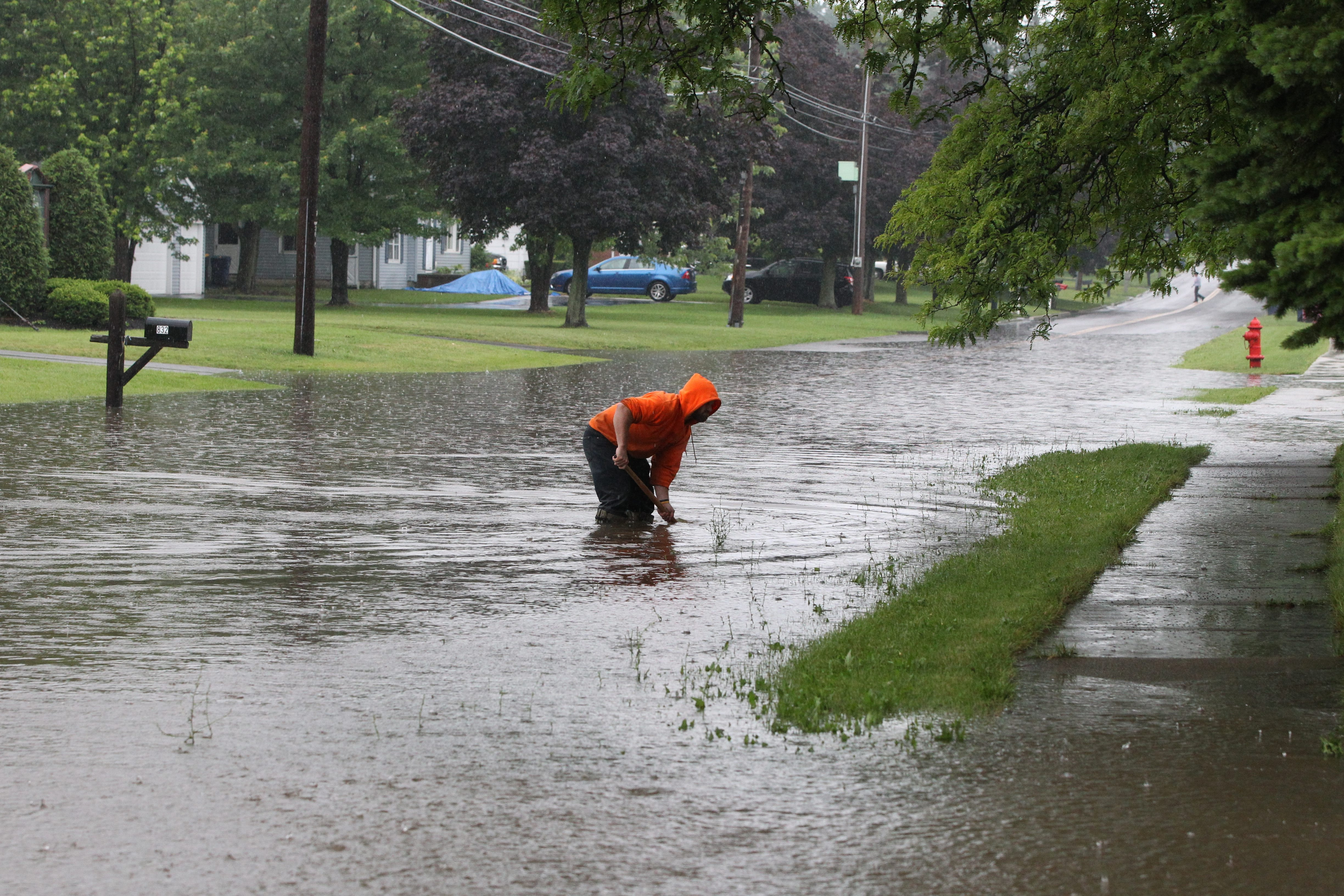 Mark Haenle , a city worker, cleans out the cogged drain on East High and Stevens in Lockport,NY on Friday, June 28, 2013.  {James P. McCoy/ Buffalo News}