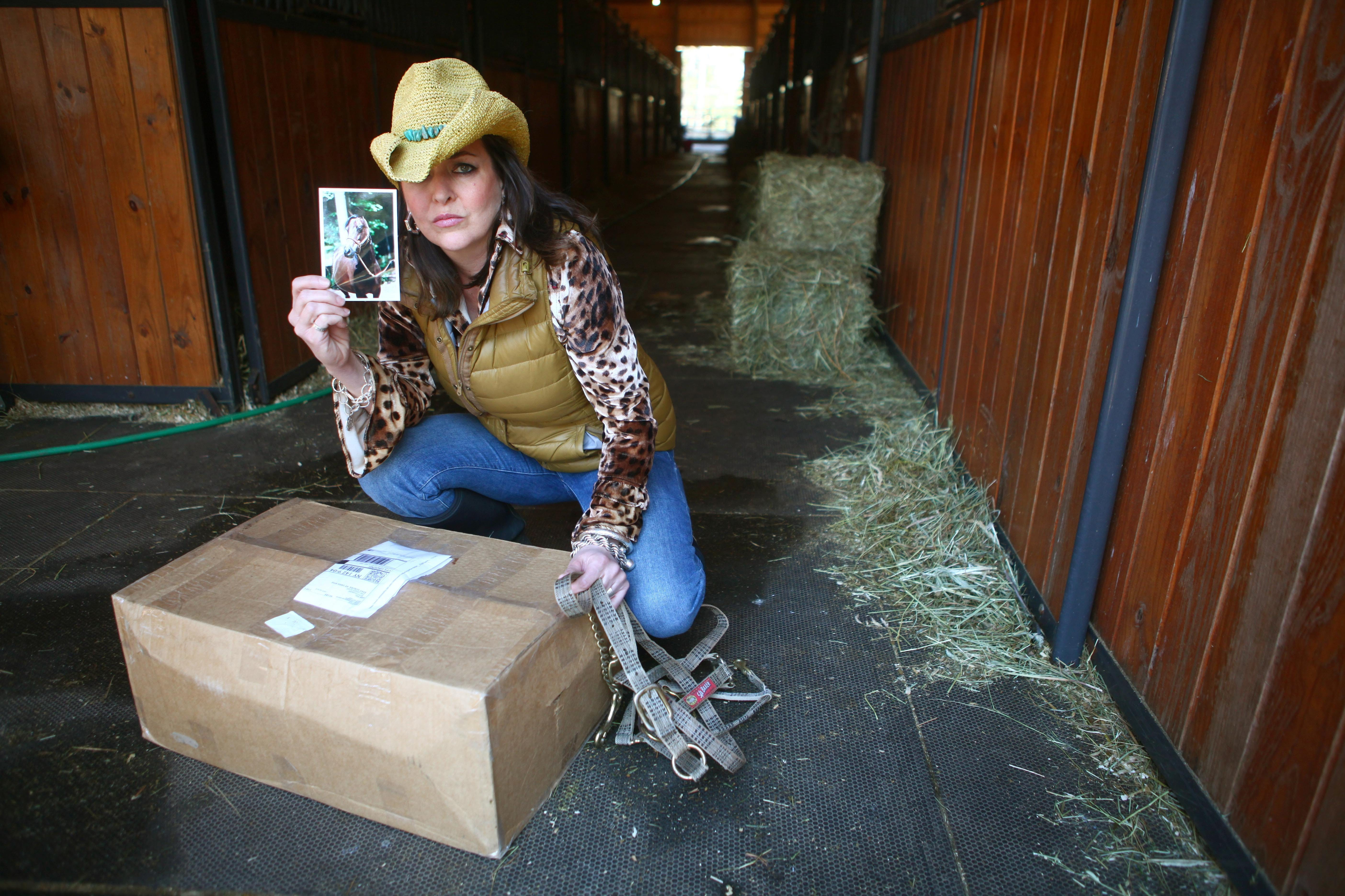 Beth Lynn Hoskins, in 2012, holds sentimental photograph as she kneels beside box containing ashes of one of her horses that died. Her trial on animal-cruelty charges is being delayed amid continuing accusations of prosecutorial misconduct.