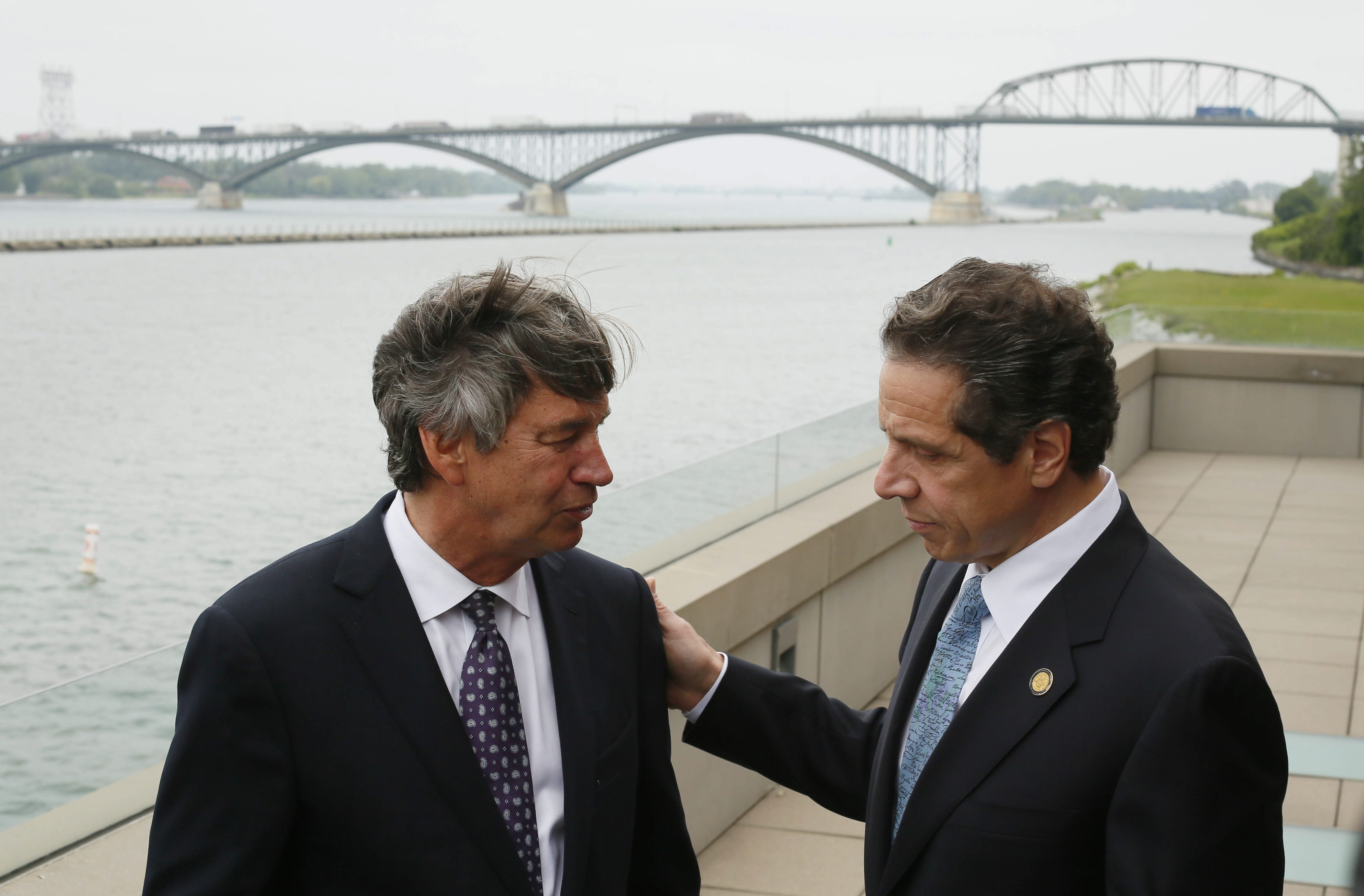 Canadian Ambassador Gary Doer, left, and New York Gov. Andrew Cuomo chat following the announcement of an agreement between New York and Canada on the Peace Bridge, background, at the Frank Lloyd Wright Boathouse at the West Side Rowing Club, Wednesday, June 26, 2013. (Derek Gee/Buffalo News)