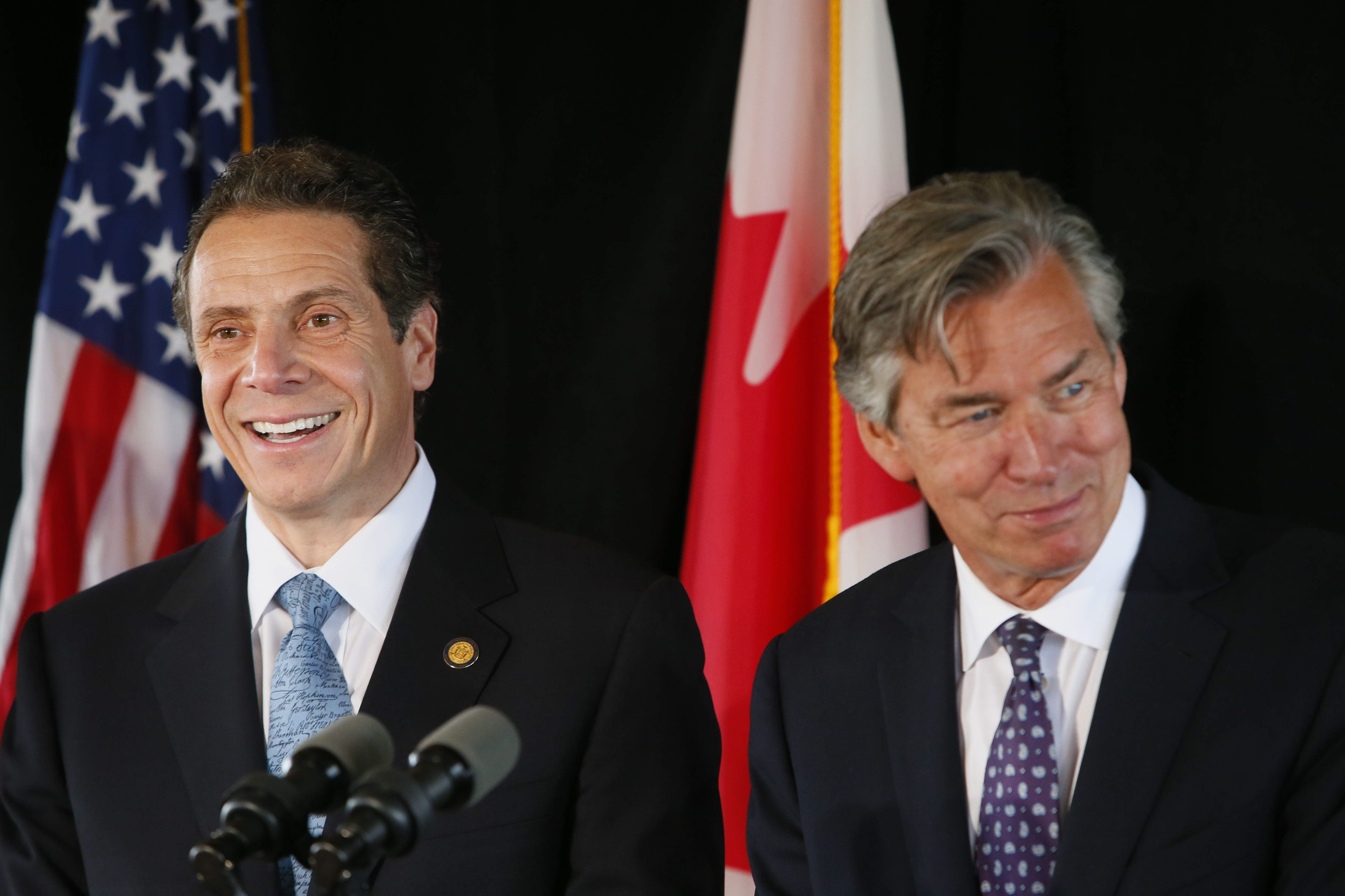 New York Gov. Andrew Cuomo, left, and Canadian Ambassador to the U.S. Gary Doer, right, have a laugh during a press conference to announce an agreement between New York and Canada on the Peace Bridge at the Frank Lloyd Wright Boathouse at the West Side Rowing Club, Wednesday, June 26, 2013.  (Derek Gee/Buffalo News)