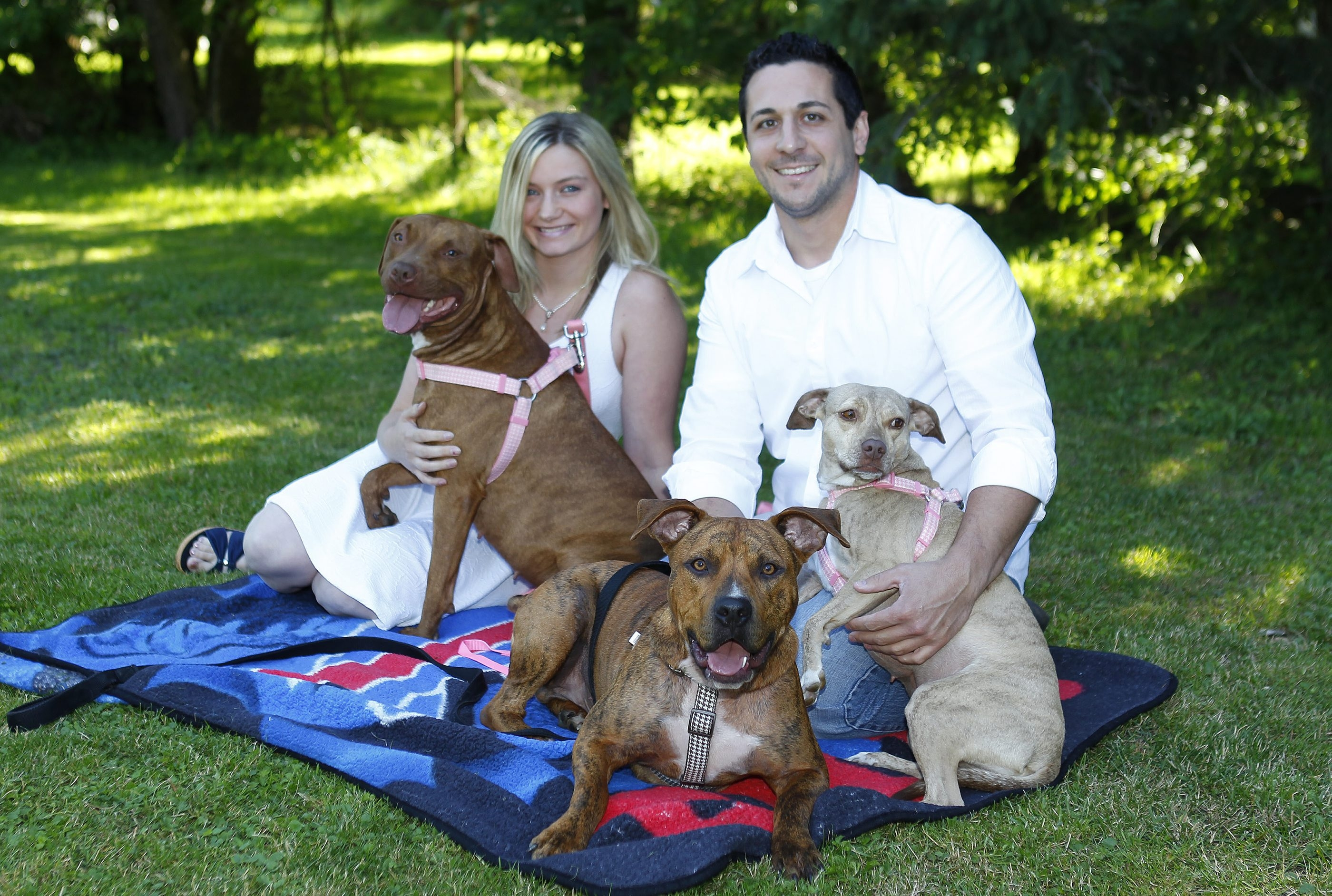 Heather VanDette sits with Maggie, a dog she hesitated to adopt, while Vinny Marano holds Mocha. Logan is in front.