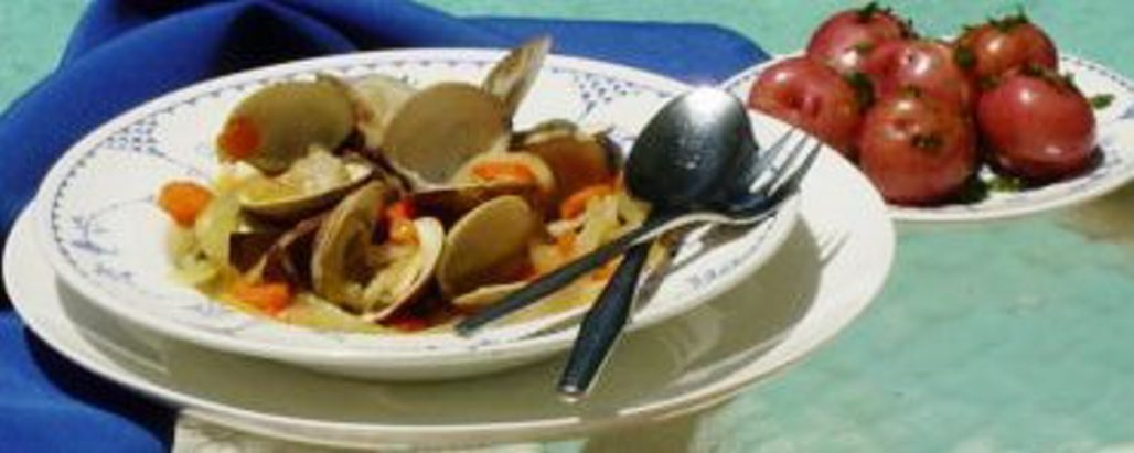 A large bowl of steamed clams, some parsley potatoes and a chilled glass