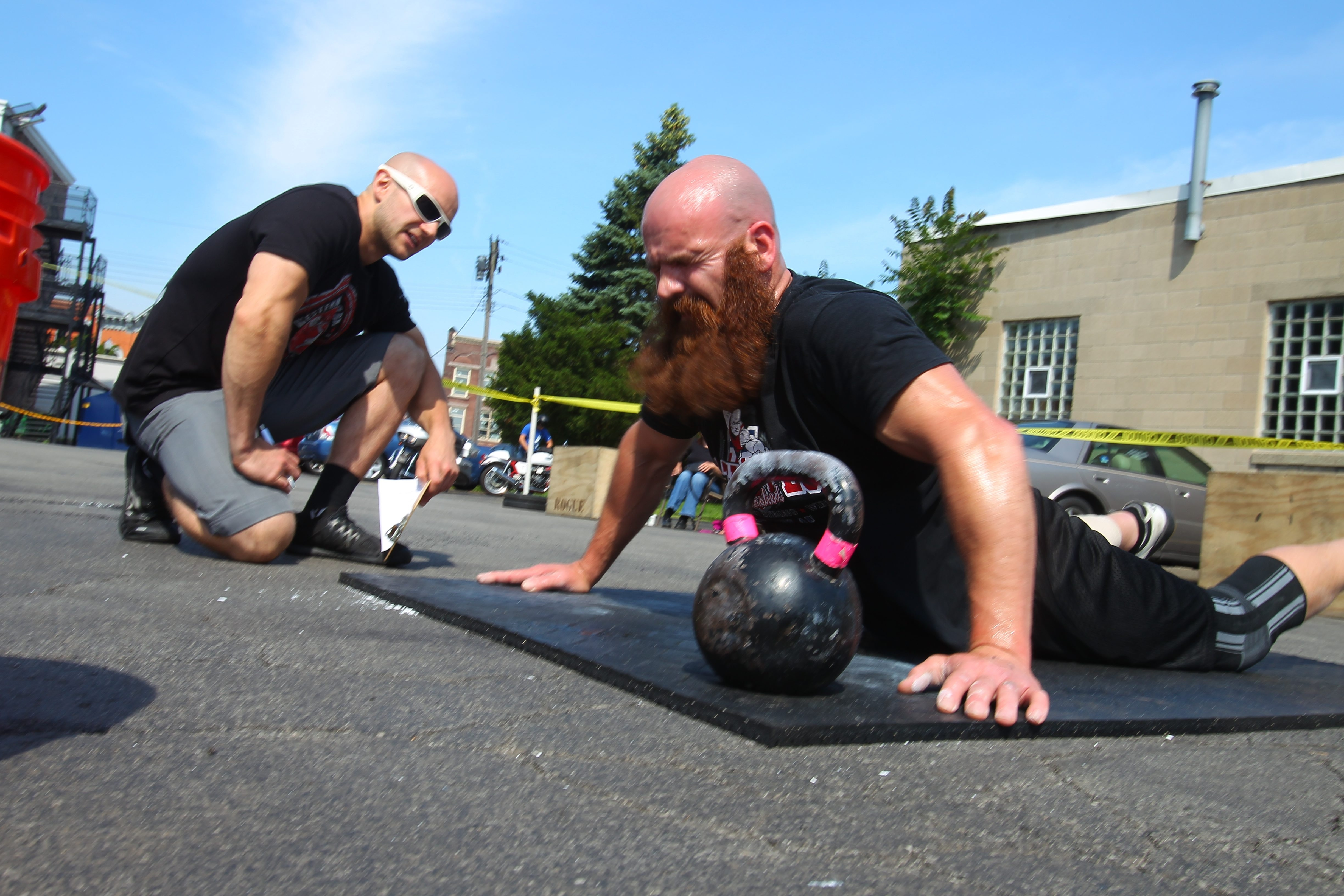 Robby Dinero, of Holland, competes in the WNY Summer Classic doing a nine-minute series of 10 squats, 20 kettlebell swings and 10 pushups in the parking lot at North Tonawanda's Gateway Center.