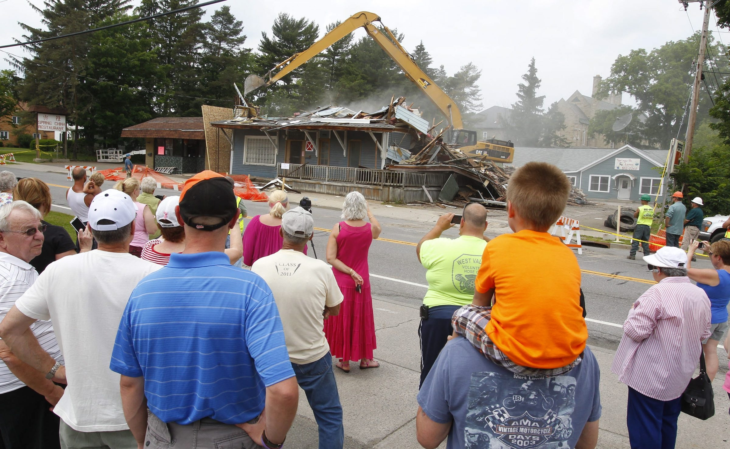 Residents gather Saturday to watch workers demolish the former Springville Hotel, whose walls and floors were near collapse, prompting its demolition.