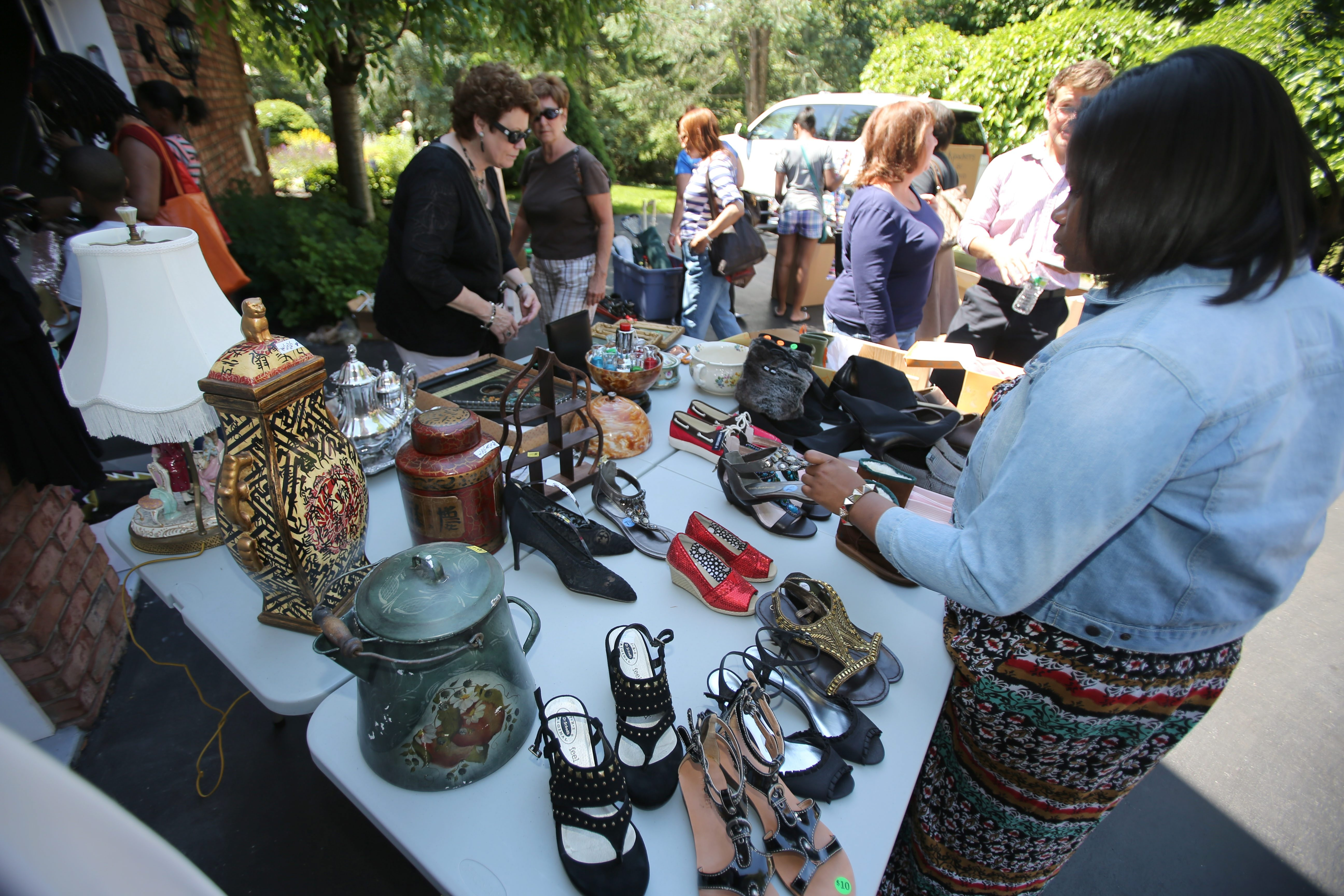 Potential customers look over a table of shoes and decorative items at a yard sale in the Spaulding Lake neighborhood Friday in Clarence. The annual sale continues today in the upscale community.