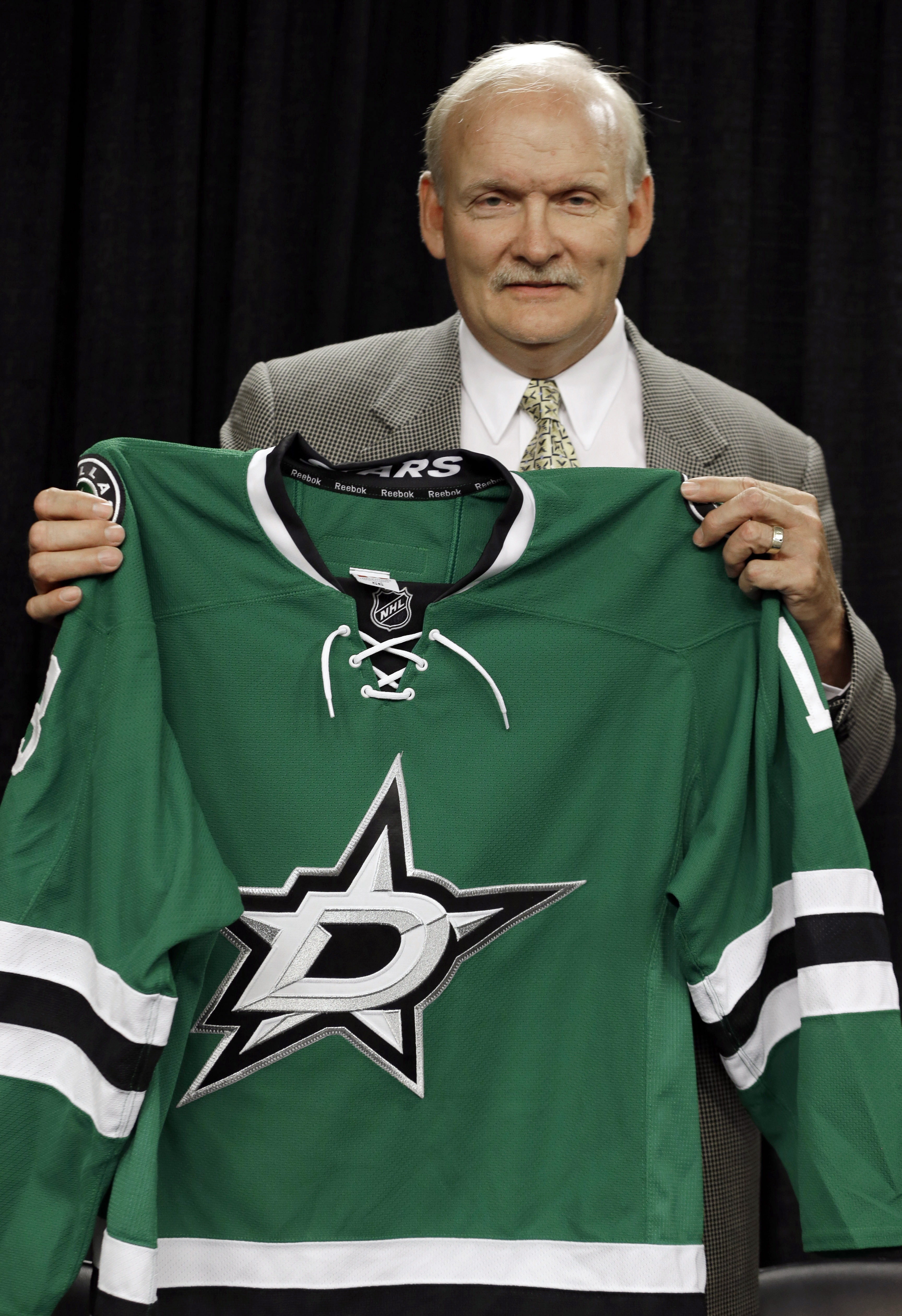 New coach Lindy Ruff with the redesigned Dallas Stars jersey.