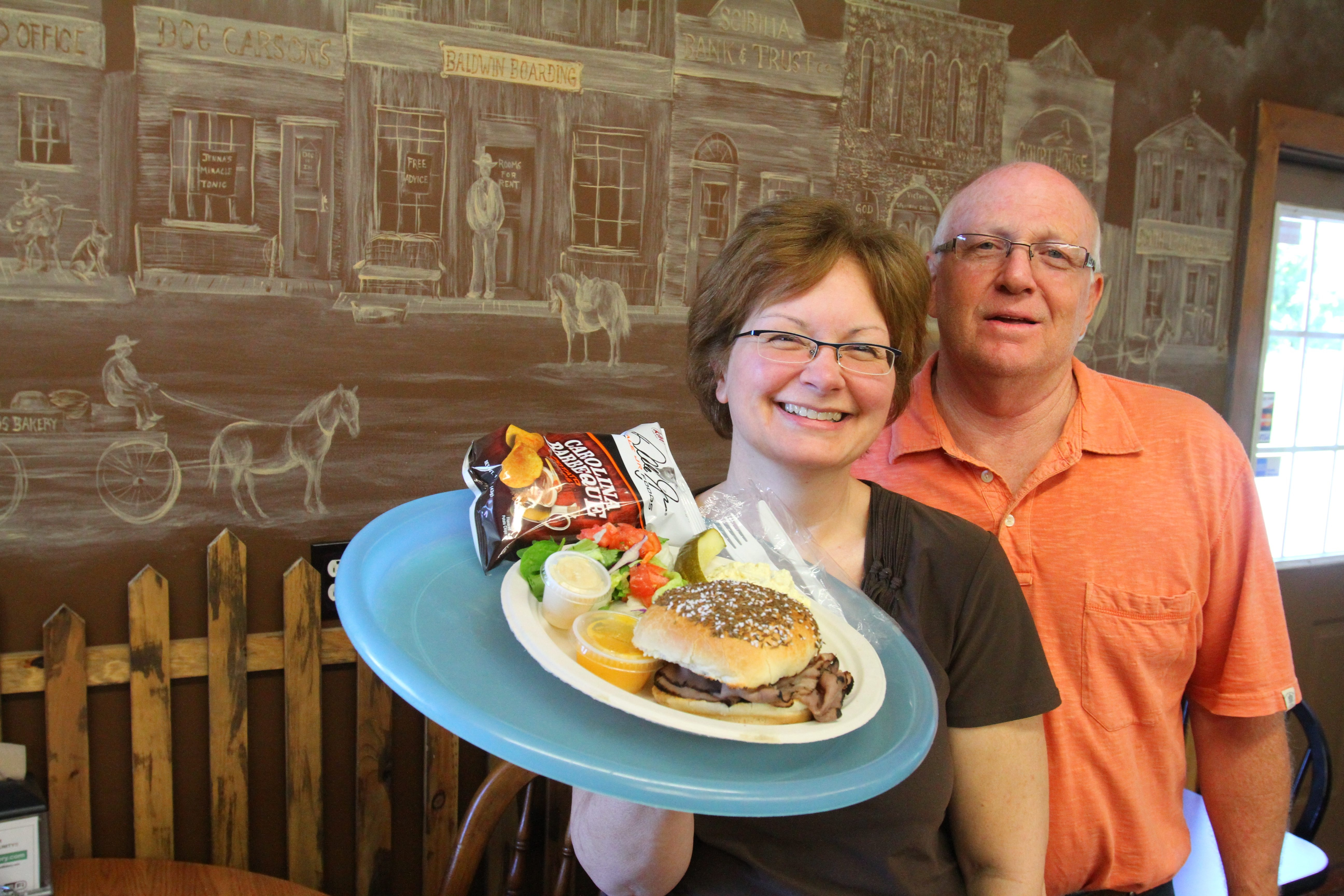 Gwen and Dave Carson with a  their   Roast Beef on Weck Special with Salad Chips Pickle and Potato Salad  at Carson's Country Deli and Bakery.