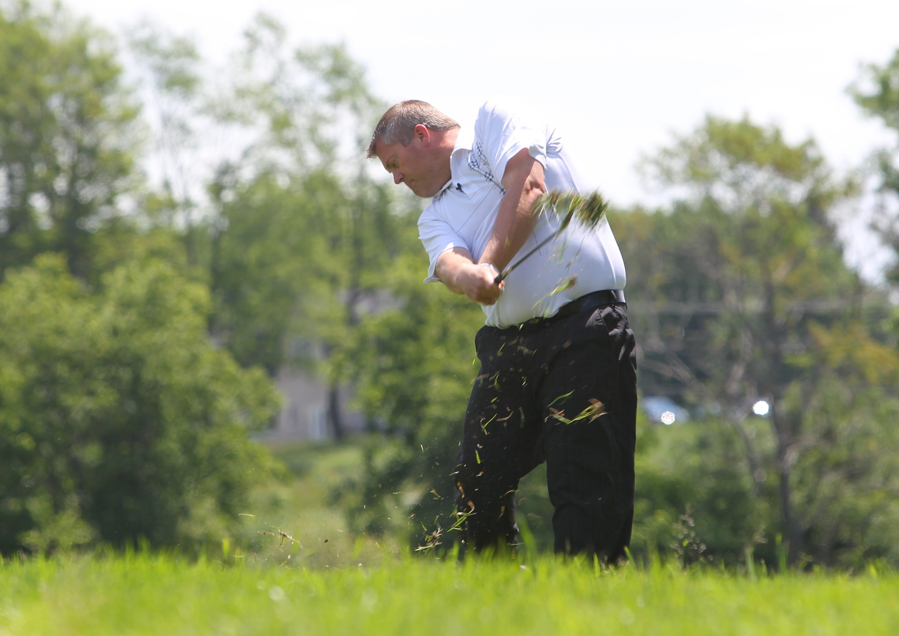 Harvest Hill's Scott Arnold demonstrates how to hit from the high rough at the club in Orchard Park on Tuesday.