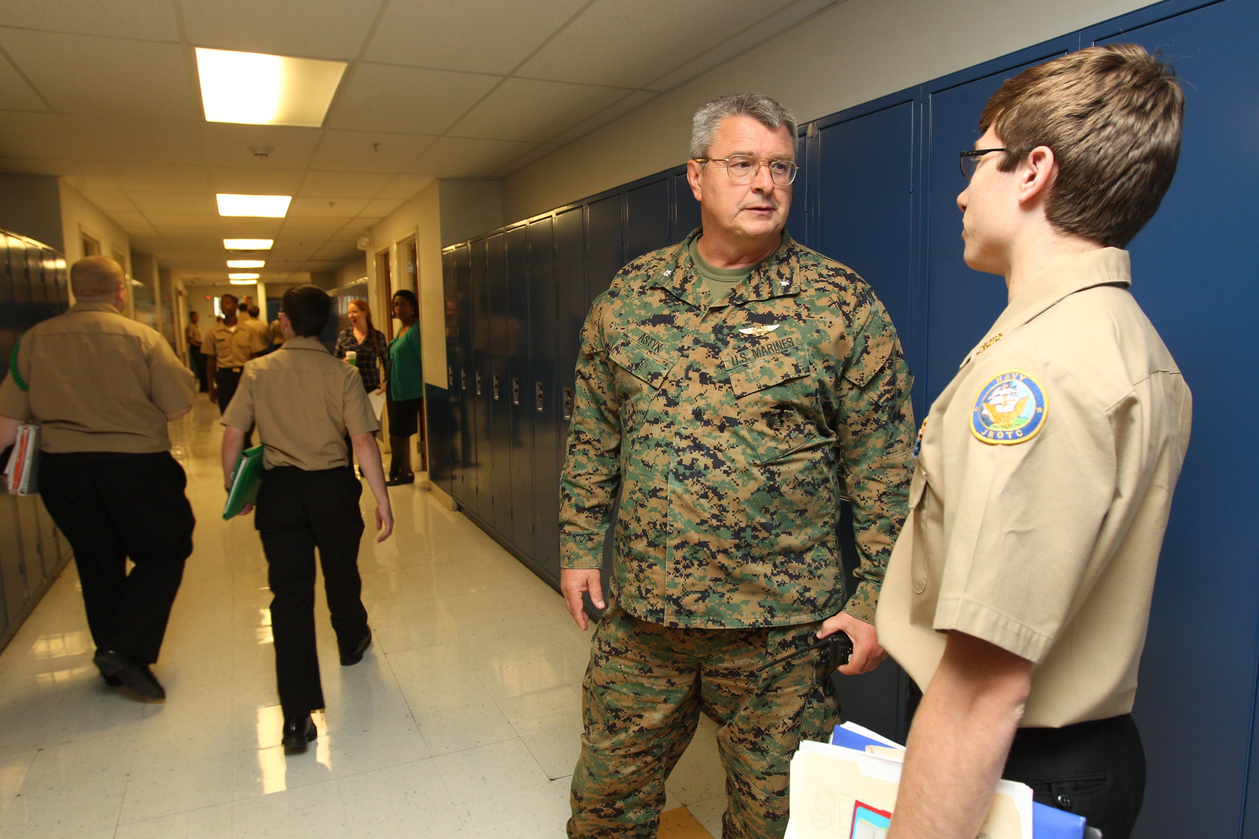 Students in Dawn Krol's math class wear the uniform of the Navy Junior ROTC; seniors wear the school polo and class hoodie. Above, Commandant Lawrence Astyk talks with student Joe Montalbano; below, Spencer Rhyans, left, and Alexis Spikes inspect their shipmates' uniforms as students arrive at school.