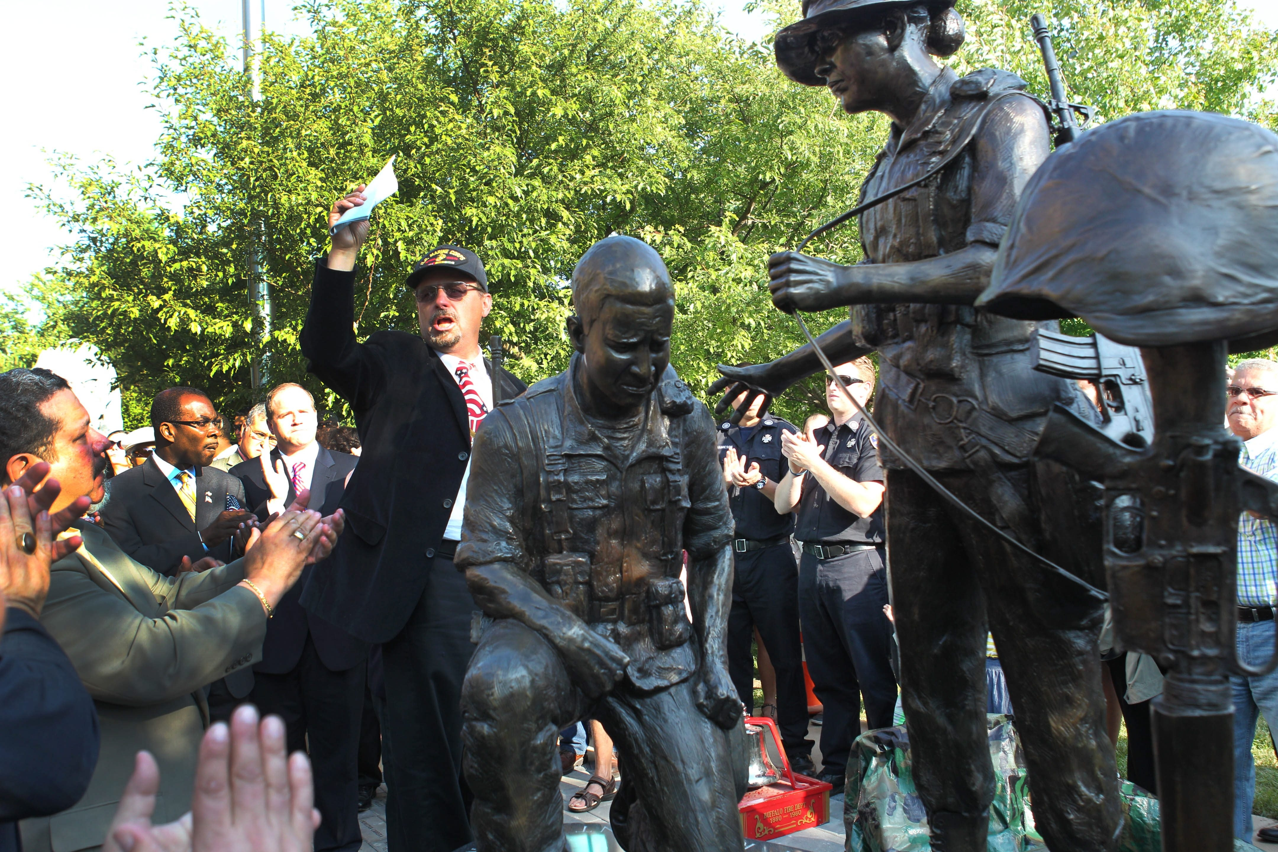 The region's first monument honoring Hispanic-American military veterans was unveiled Friday at the Buffalo and Erie County Naval & Military Park. Jose Pizarro, center, chairman of the local memorial committee, pays tribute to all Hispanics who have served.  For a photo gallery, go to BuffaloNews.com.