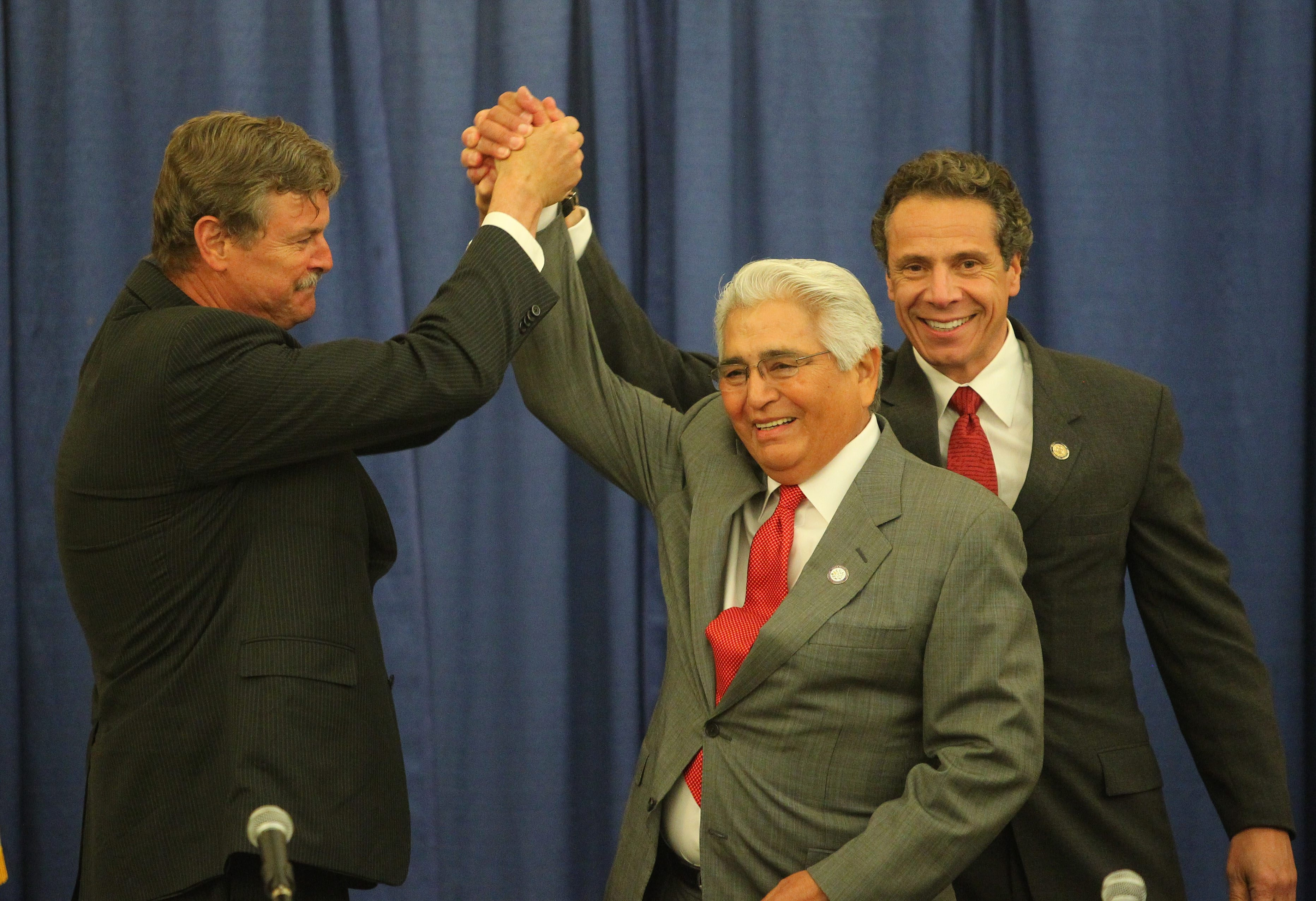 From left, Niagara Falls Mayor Paul Dyster clasps hands with Seneca Nation President Barry Snyder and New York State Gov. Andrew M. Cuomo after signing an agreement ending a long dispute about casino revenue sharing.