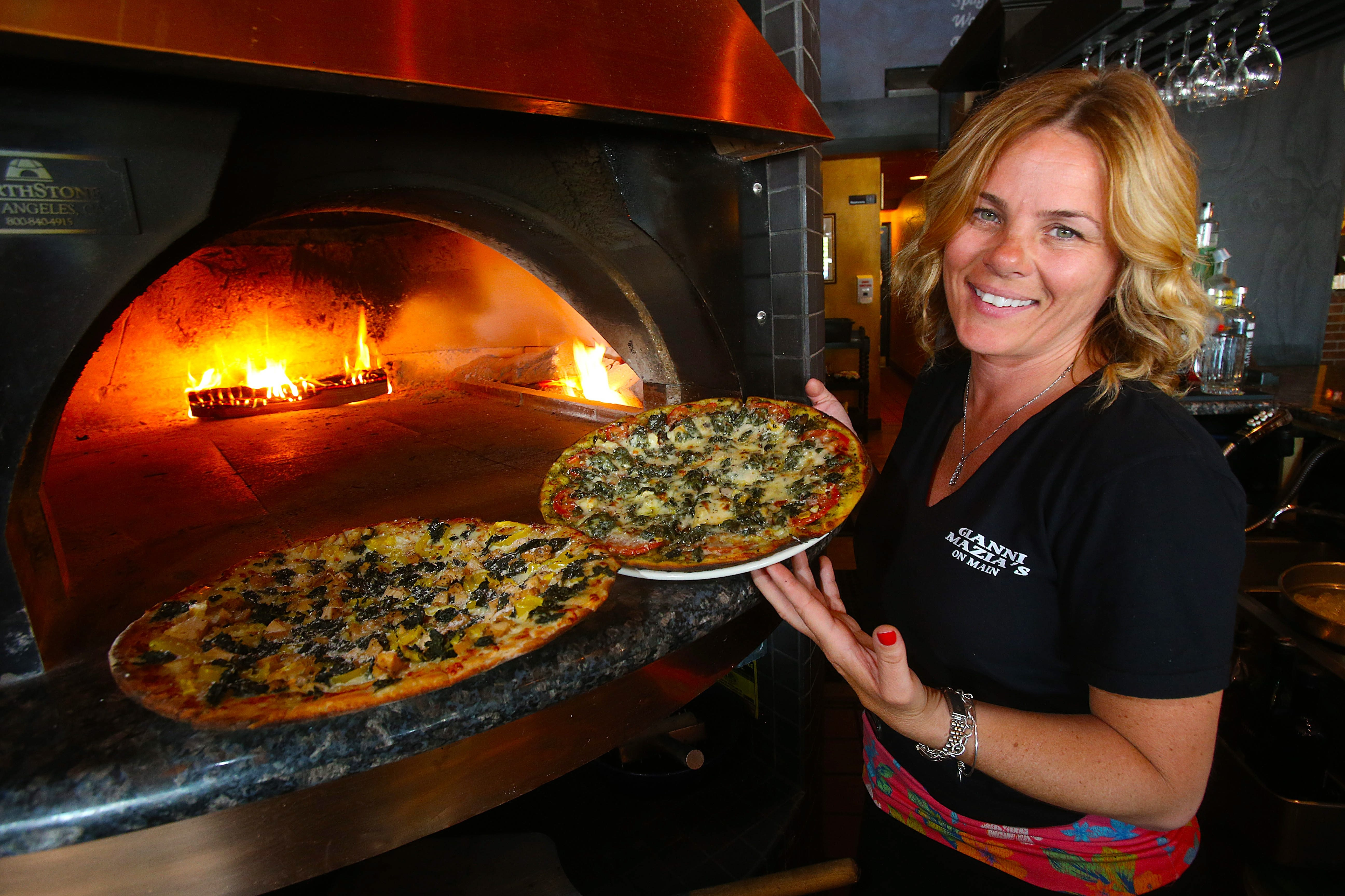 Owner Paula Cambria shows off the Desperate Housewife and the Pesto Provolone wood-fired pizzas.