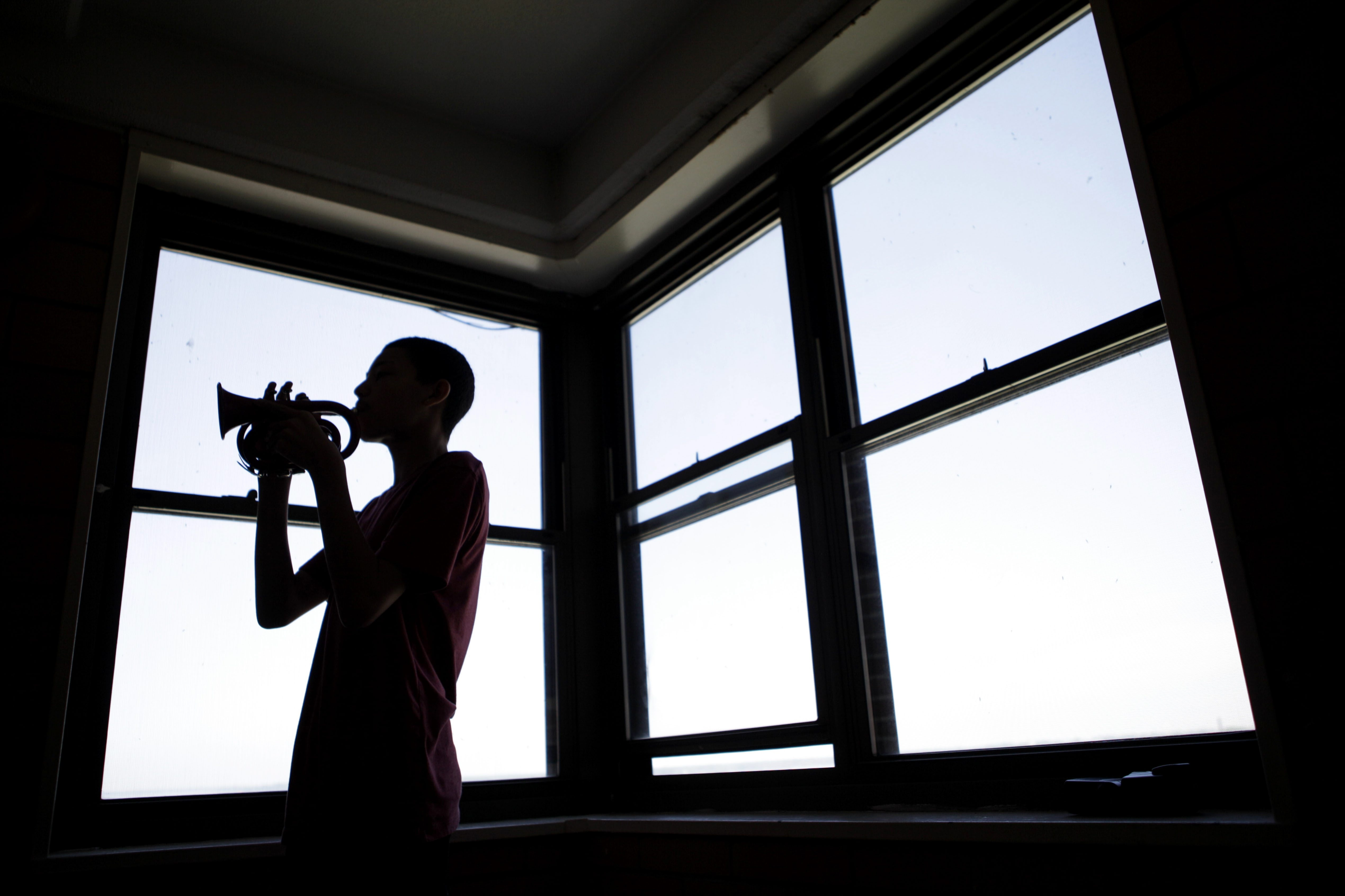 Jose Rodriguez, a 10th-grader at International Preparatory School where the award-winning band program is being eliminated, practices in his family's apartment.