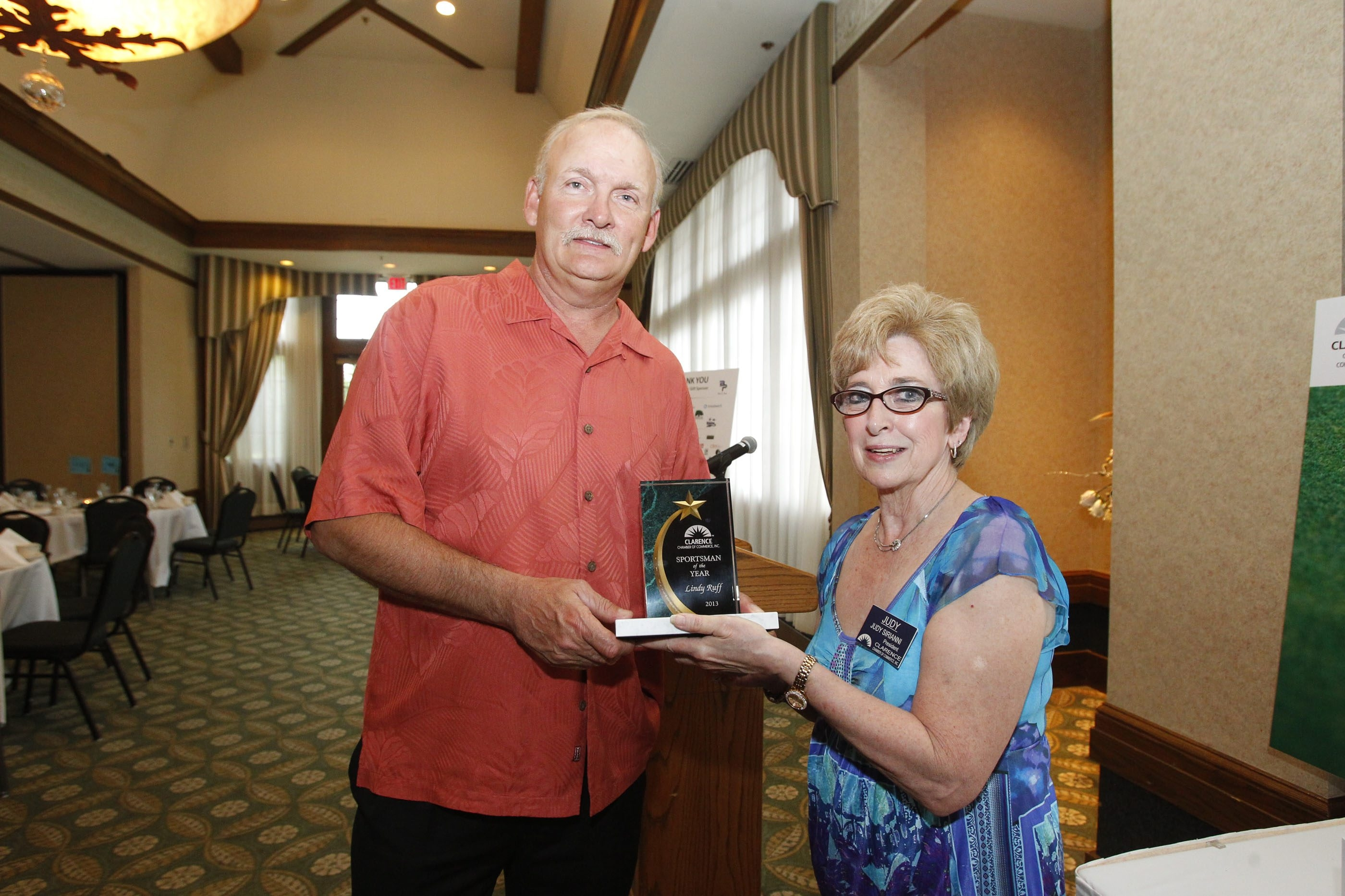 Ex-Buffalo Sabres coach Lindy Ruff receives the inaugural Clarence Sportsman of the Year Award from Judy Sirianni, the president of the Clarence Chamber of Commerce, at Westwood Country Club on Monday.
