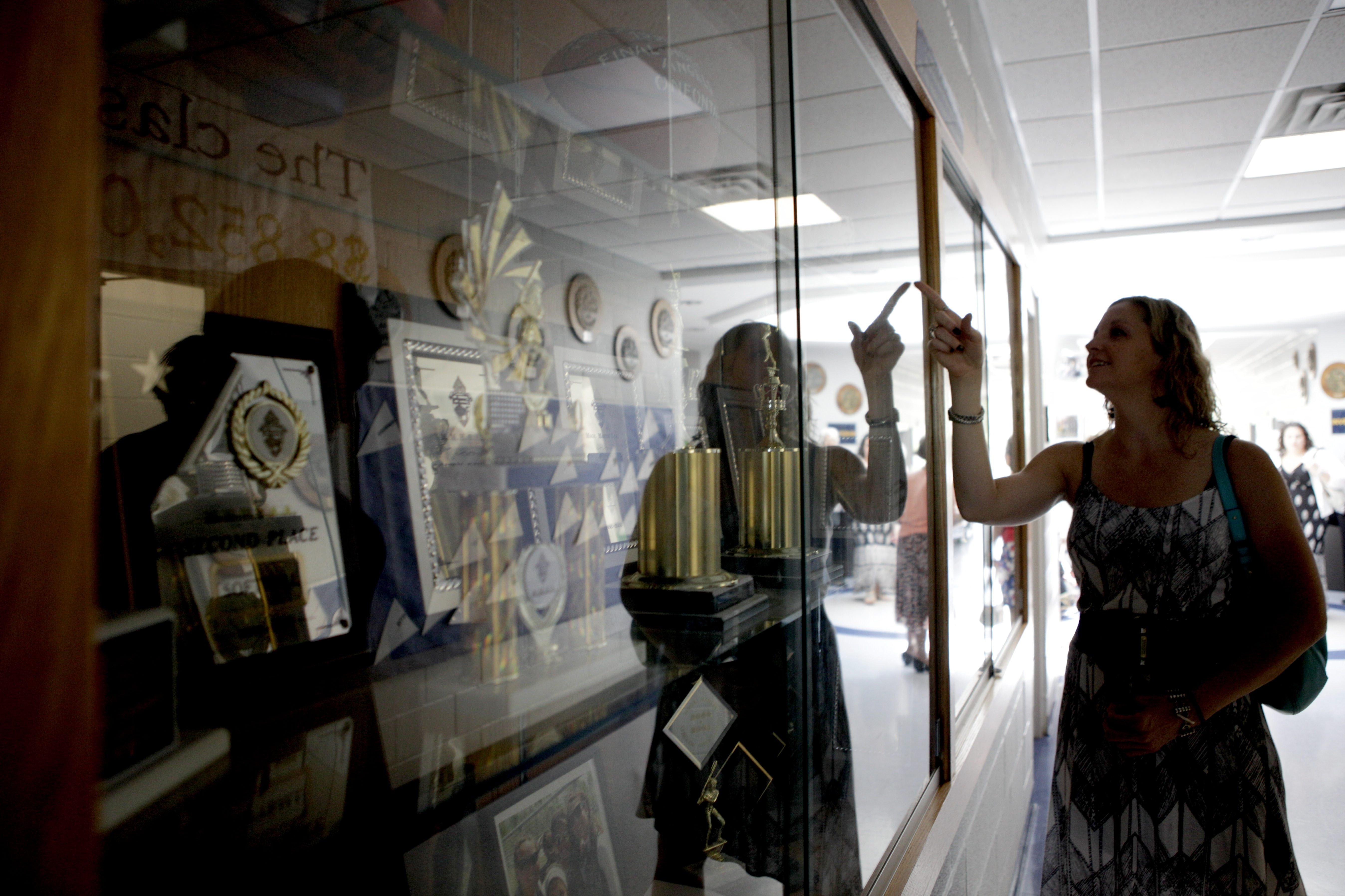 Sarah Blanchard looks at trophies in the Holy Angels Academy display case during a reception commemorating the school's closing.