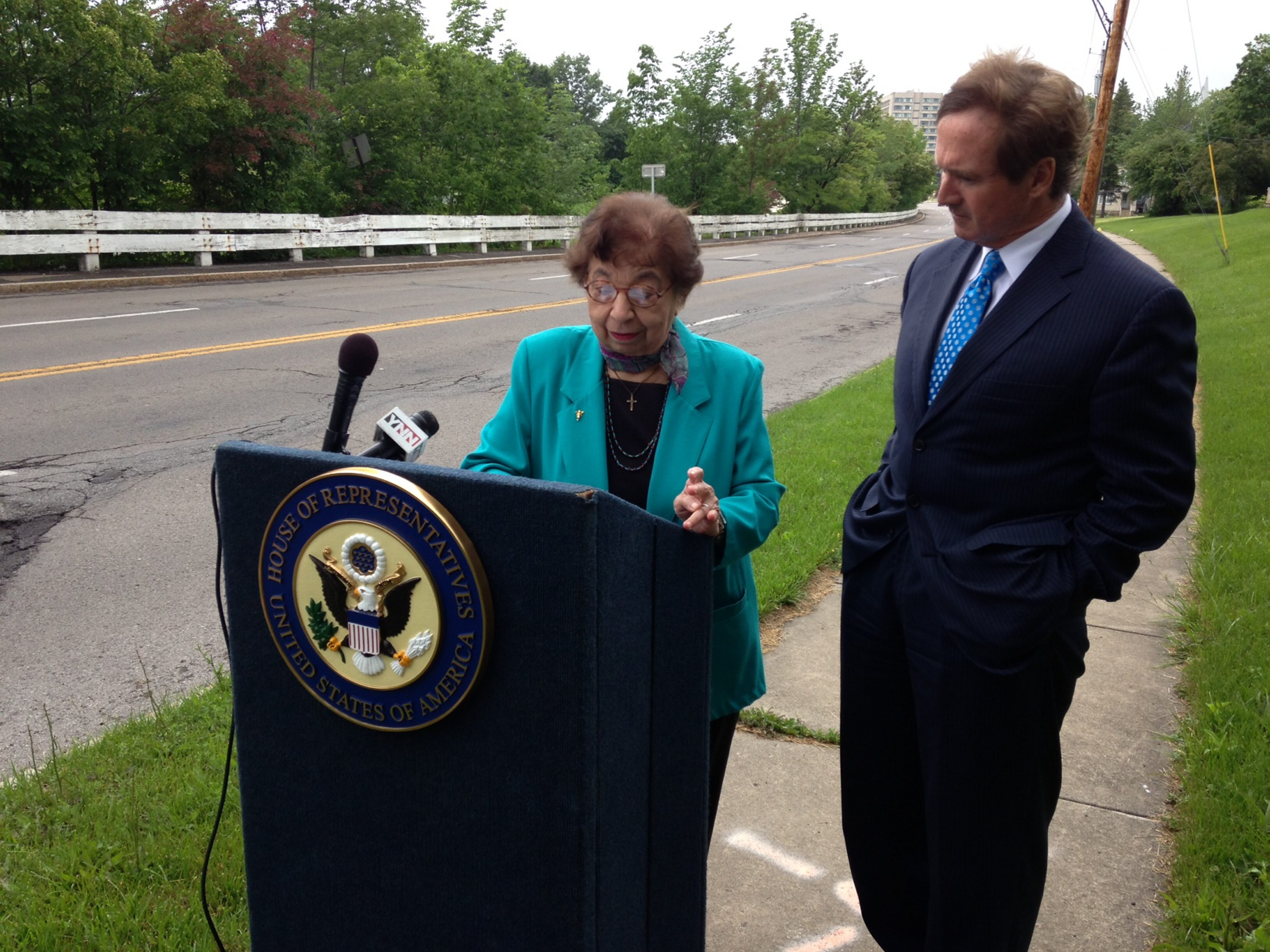 Mamie Simonson and Rep. Brian Higgins speak Friday near the site of her home, which was demolished in 1959 to clear room for the Robert Moses Parkway.