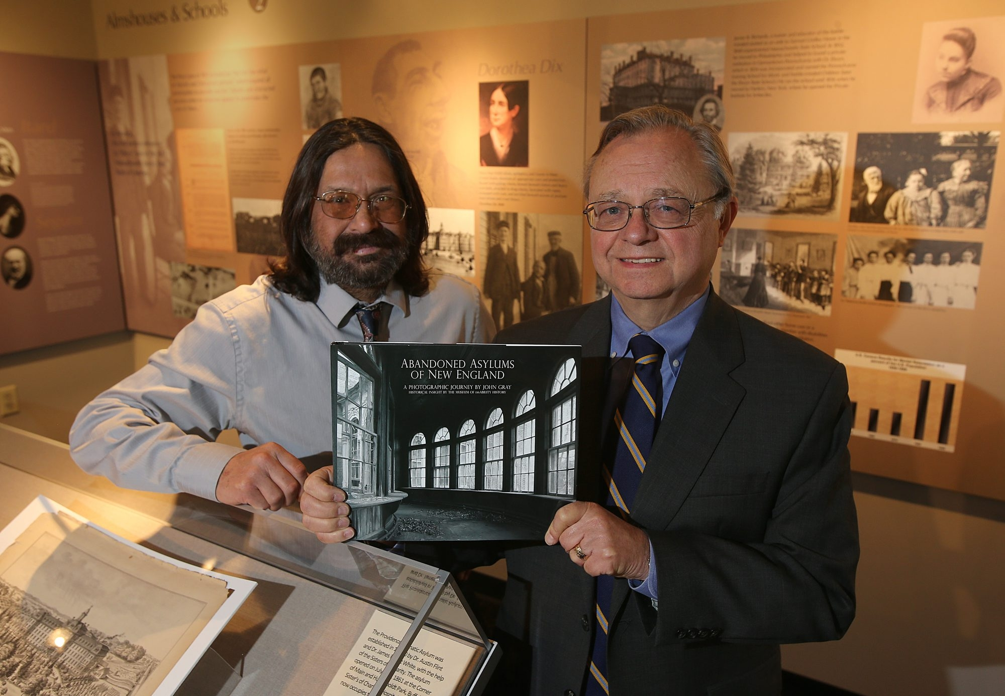 "Museum of disAbility History curator Douglas Platt, left, and James M. Boles, president and CEO of People Inc. hold a copy of ""Abandoned Asylums of New England"" at the Amherst museum."