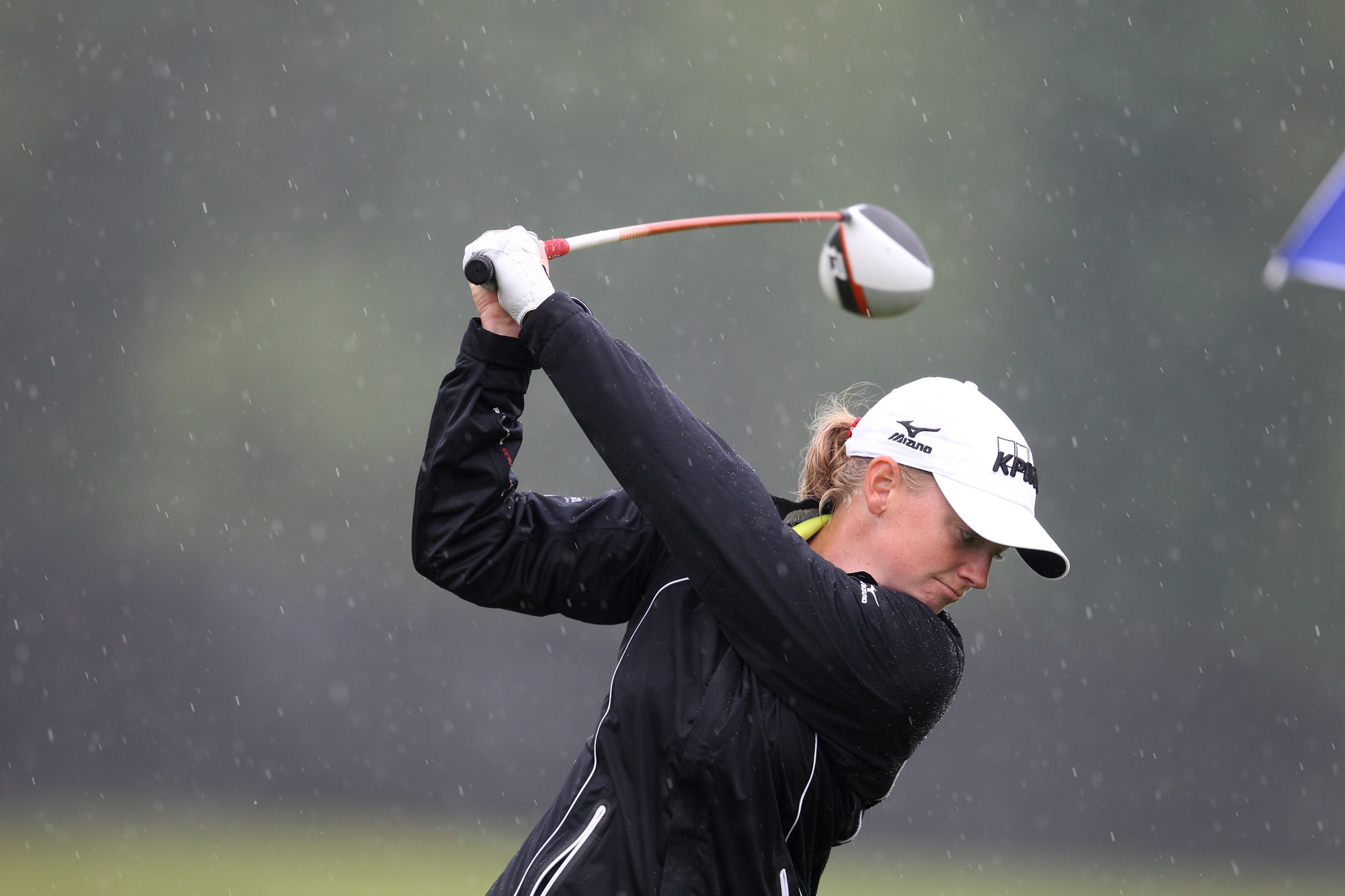Stacy Lewis swings in the rain at the driving range while waiting for the start of the weather-delayed event at Locust Hill.