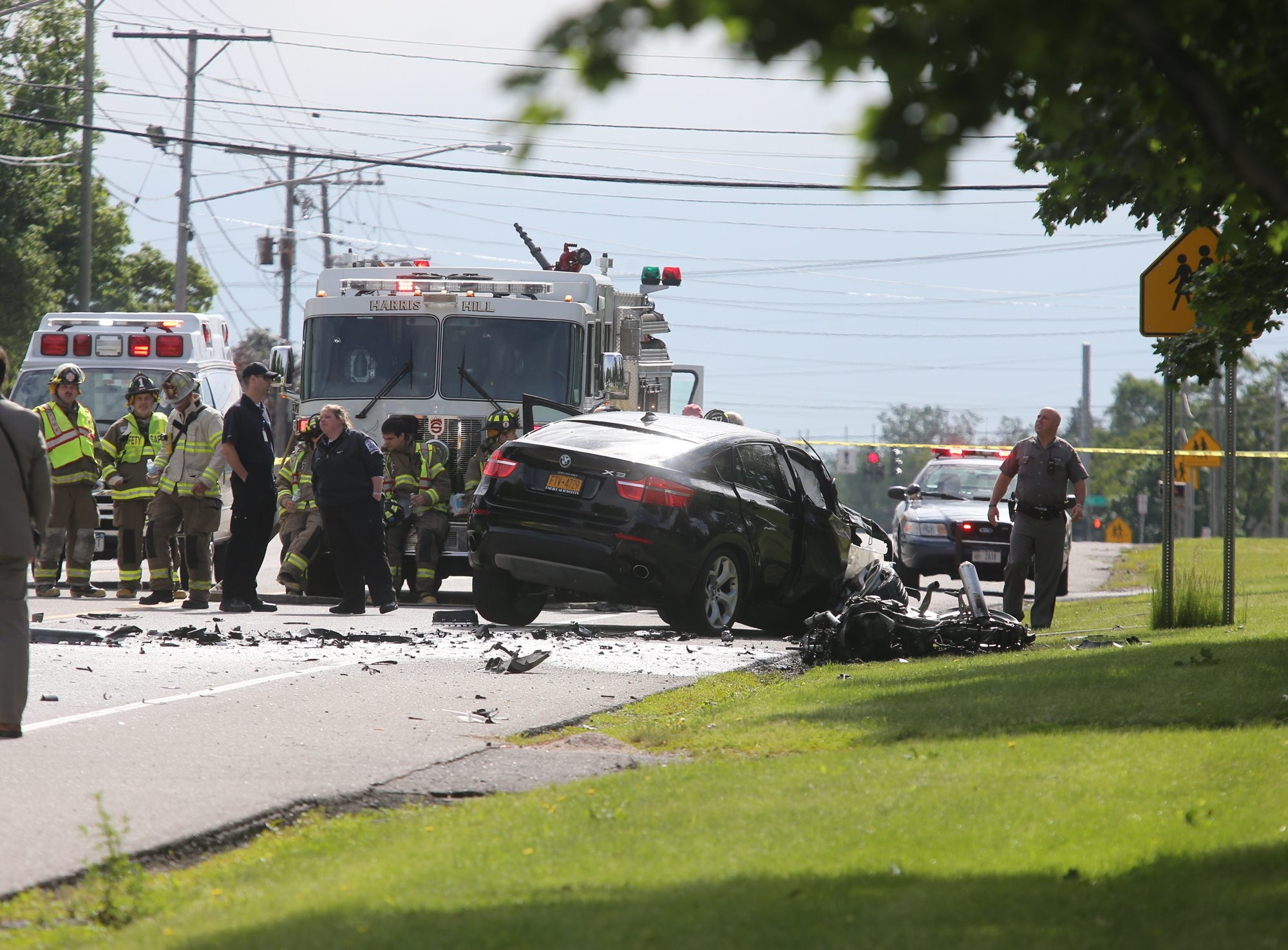 Police and fire personnel work at the scene of a collision Wednesday between a motorcycle and a BMW on Main Street in Clarence. The motorcyclist, 18-year-old Patrick S. Conway, was thrown from his bike and killed instantly, police said.