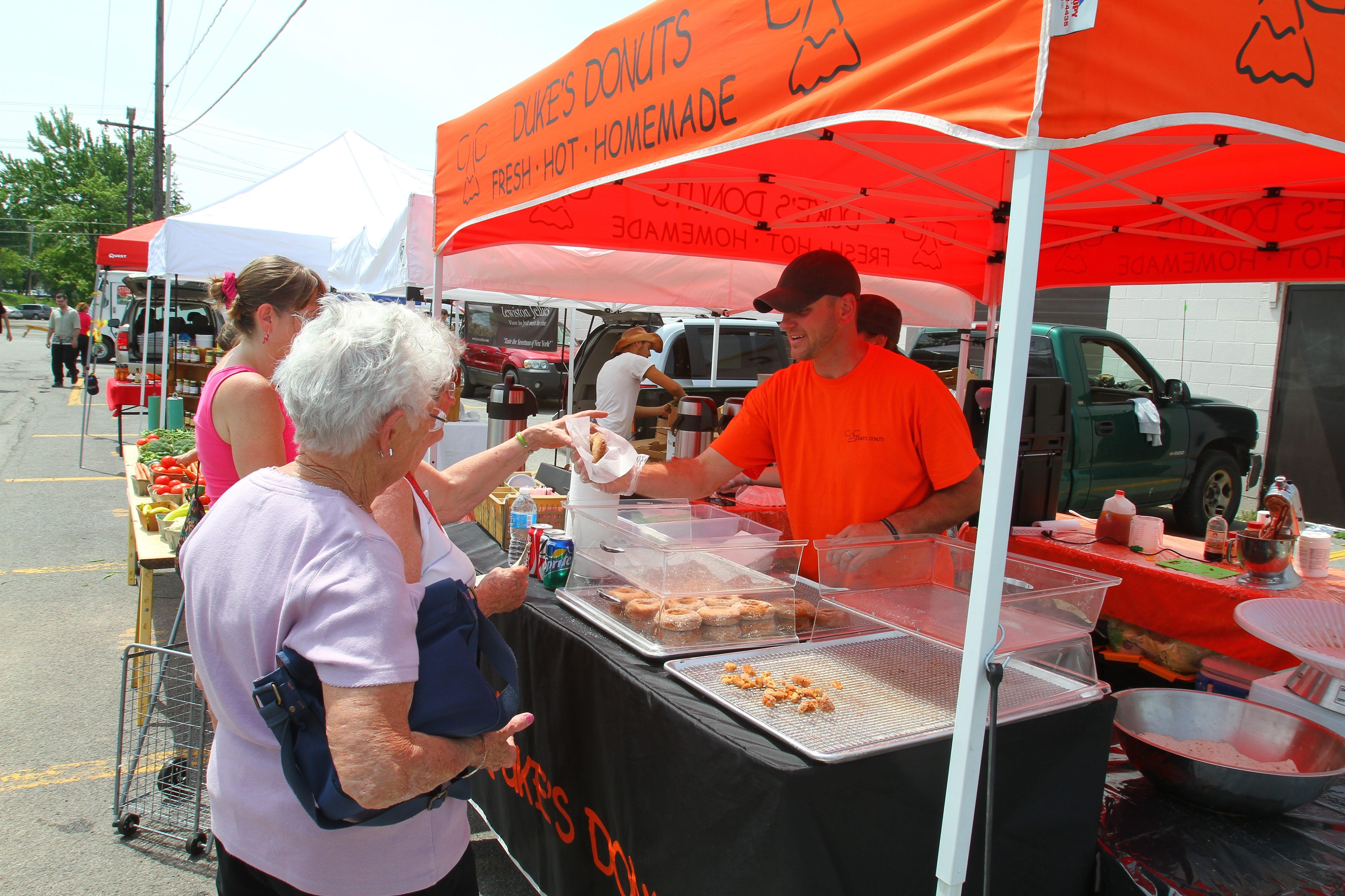 Chad Coyle, co-owner of Duke's Donuts, sells a doughnut to a customer at the Farmers' Market in North Tonawanda on Saturday. Today's farmers' markets don't sell just produce and plants.