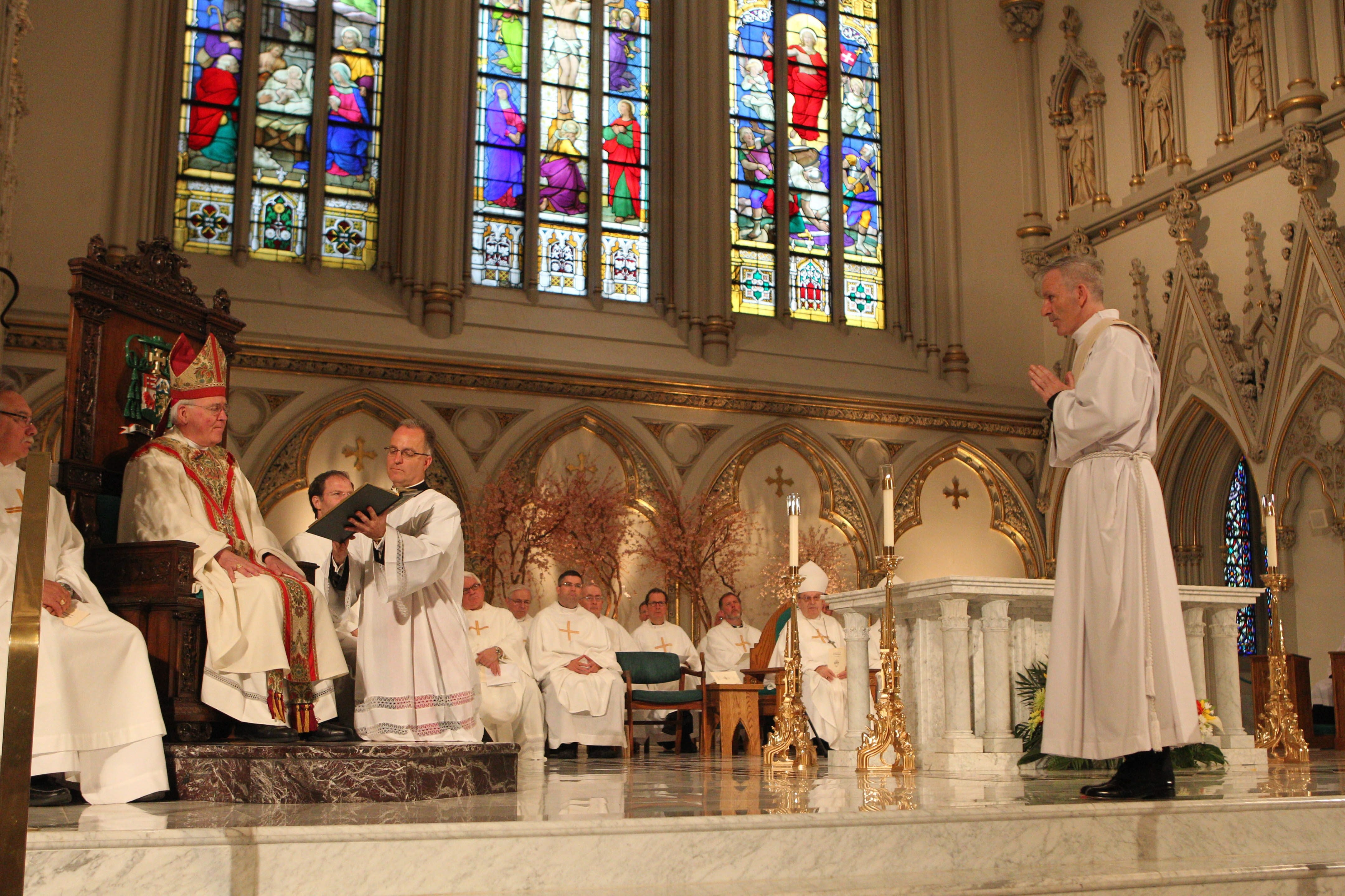 Bishop Richard J. Malone, left, listens as John E. Stanton Jr. pledges his obedience during his ordination ceremony Saturday in St. Joseph Cathedral. At age 42, Stanton is one of the youngest priests in the diocese.
