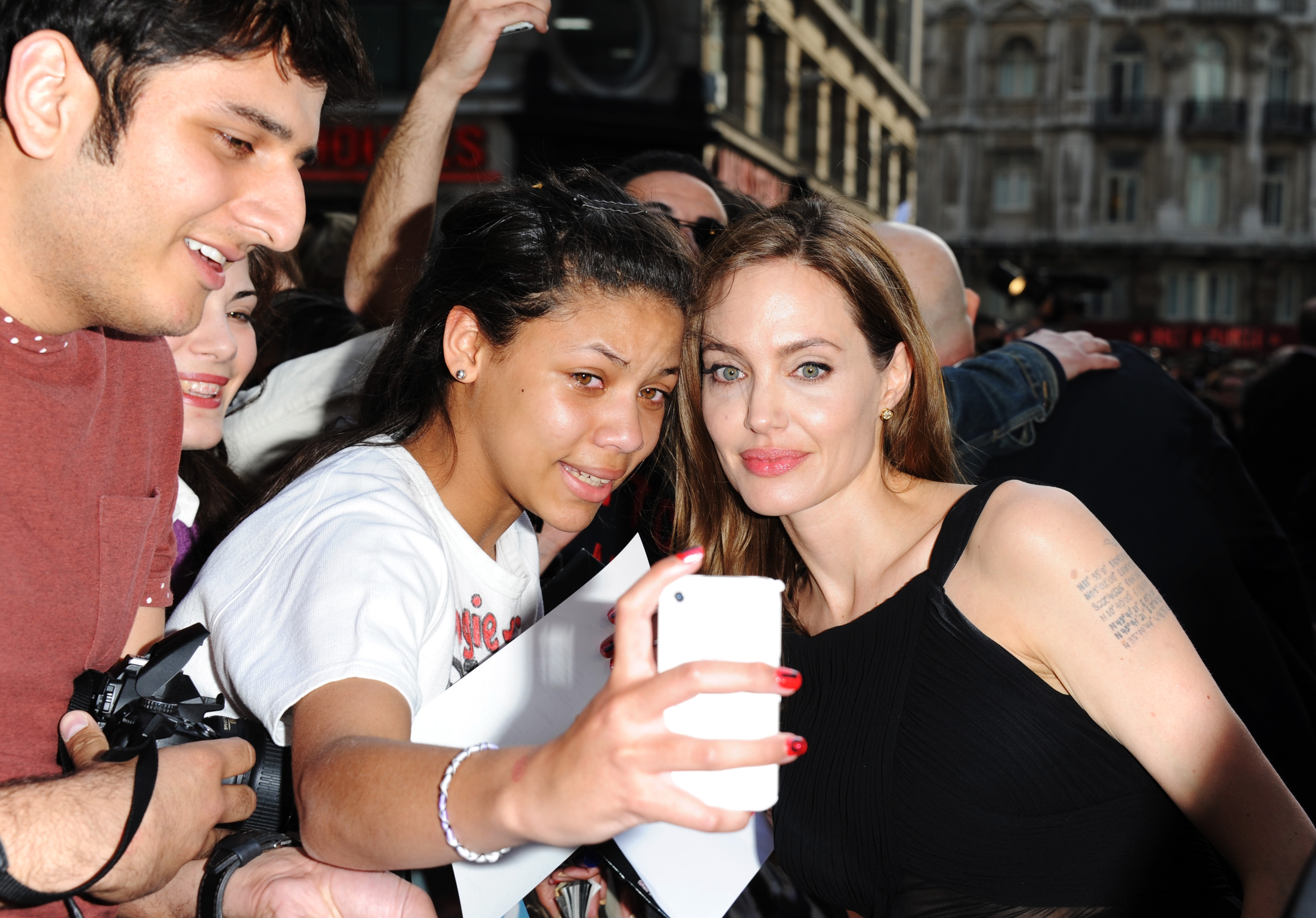 """Angelina Jolie, shown taking a picture Sunday with a delighted fan, attends the world premiere of """"World War Z"""" in London."""