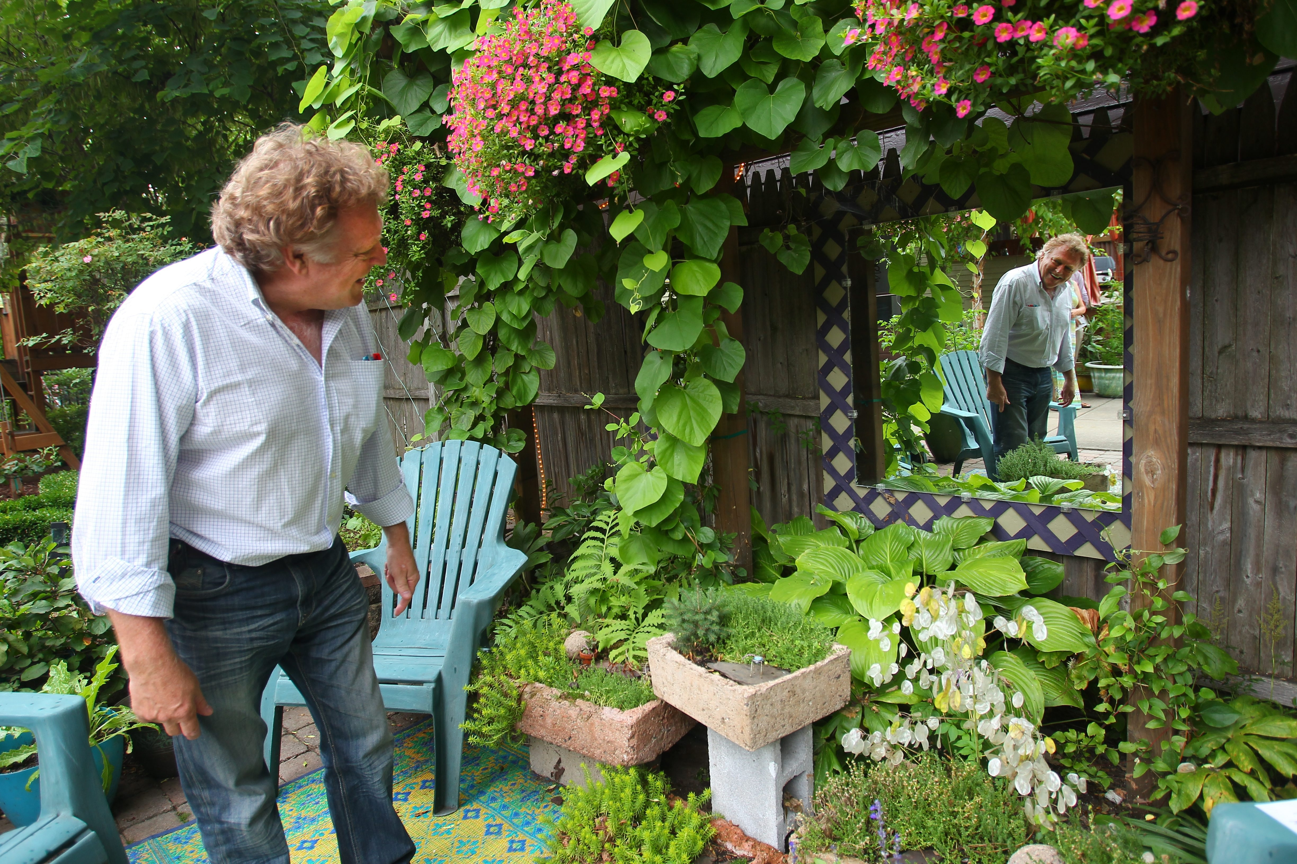 Michel Gauthier enjoys a garden on Lancaster Avenue during the 19th annual Garden Walk Buffalo Saturday.