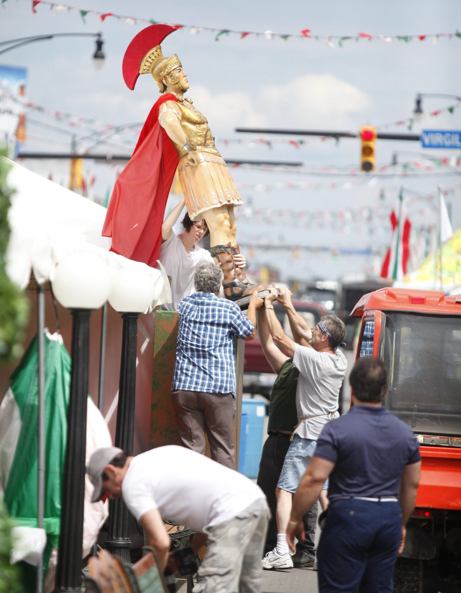 Workers set a statue into place along Hertel Avenue as preparations for the annual Italian Festival continued Wednesday.