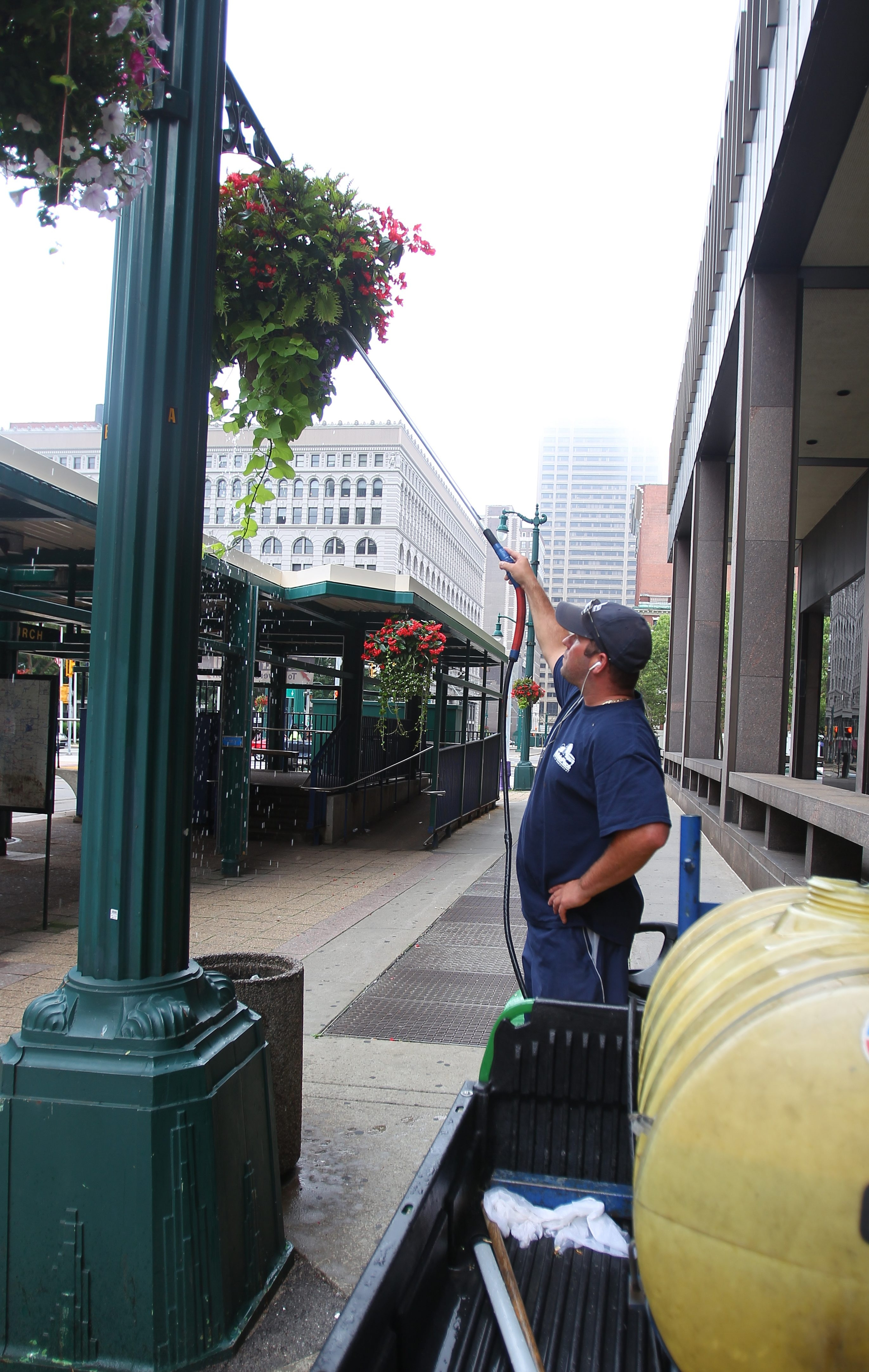 Among other services, Buffalo Place takes care of the landscaping elements on the streets within its district. Here, Bob Hastings of Buffalo Place waters planters  along Main Street in front of Main Place Mall early in July.