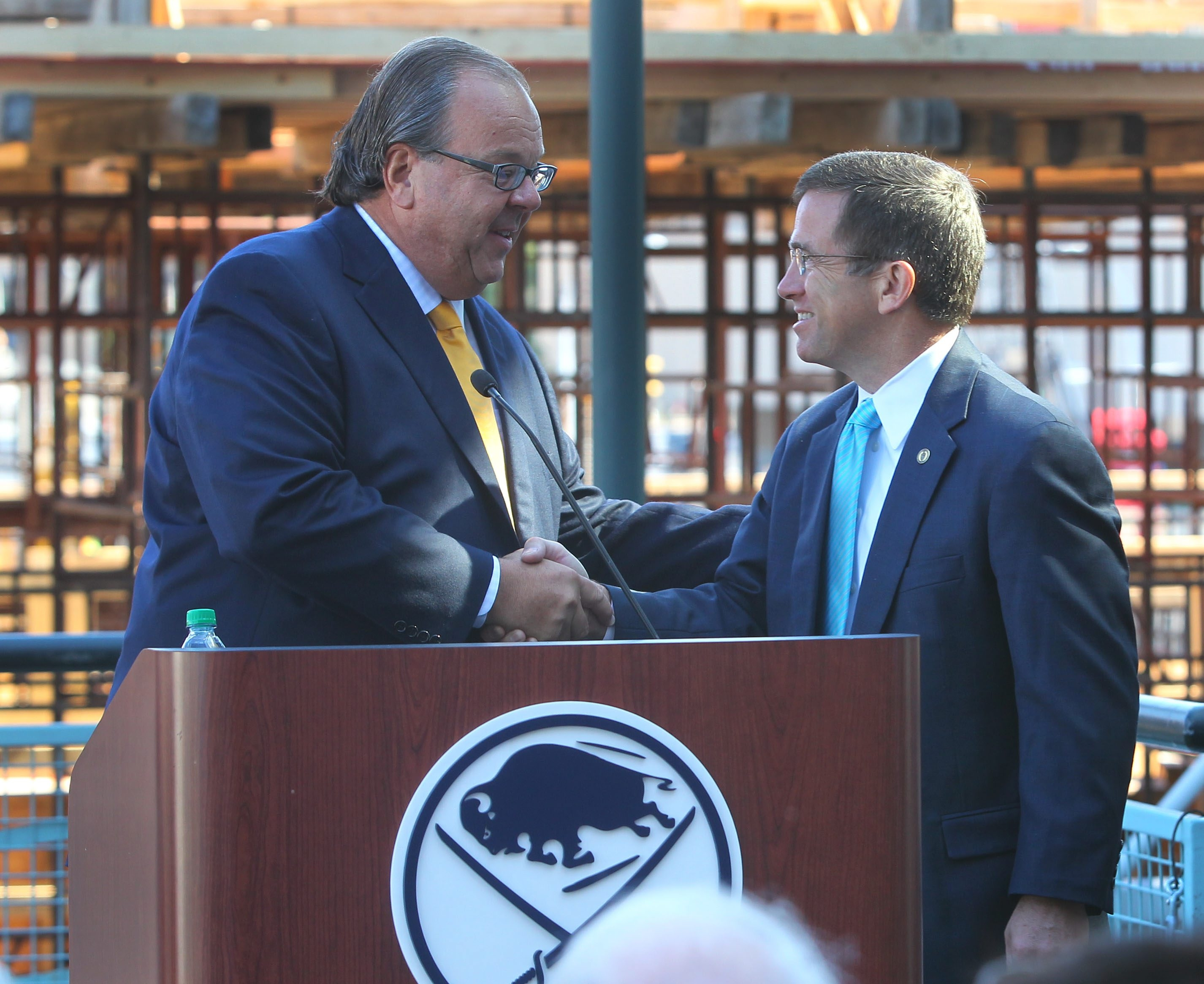 HarborCenter president John Koelmel and Canisius College president John J. Hurley greet each other during Tuesday's press conference announcing the Golden Griffins hockey team will play at the facility.