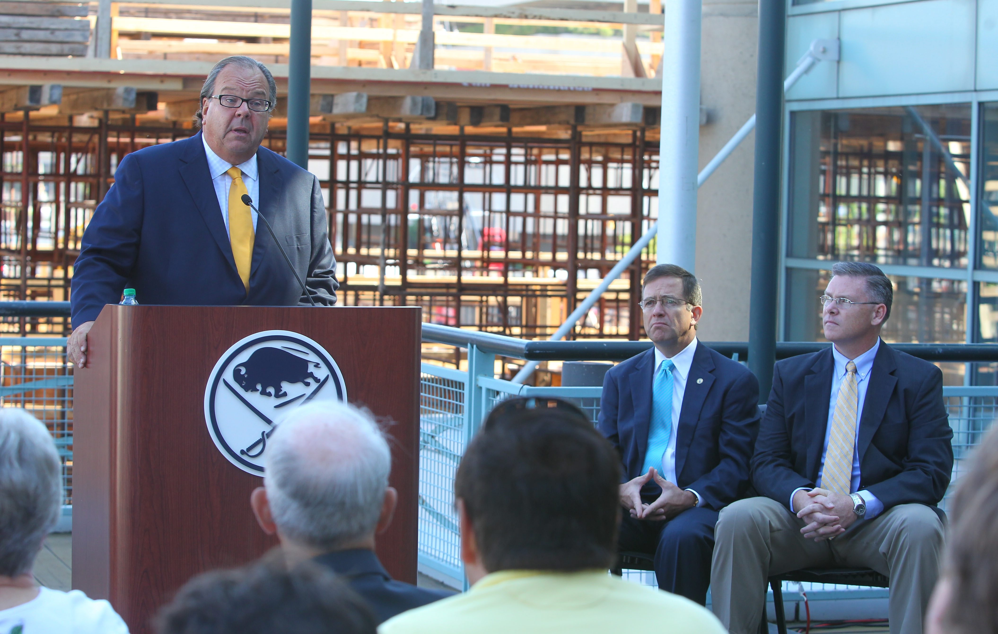 HarborCenter President John Koelmel speaks with reporters and members from Canisius College at the First Niagara Center today as he announced an agreement to have the college play all their hockey home games at the new facility when it opens in 2014.  At right is college president John J. Hurley and athletic director Bill Maher.