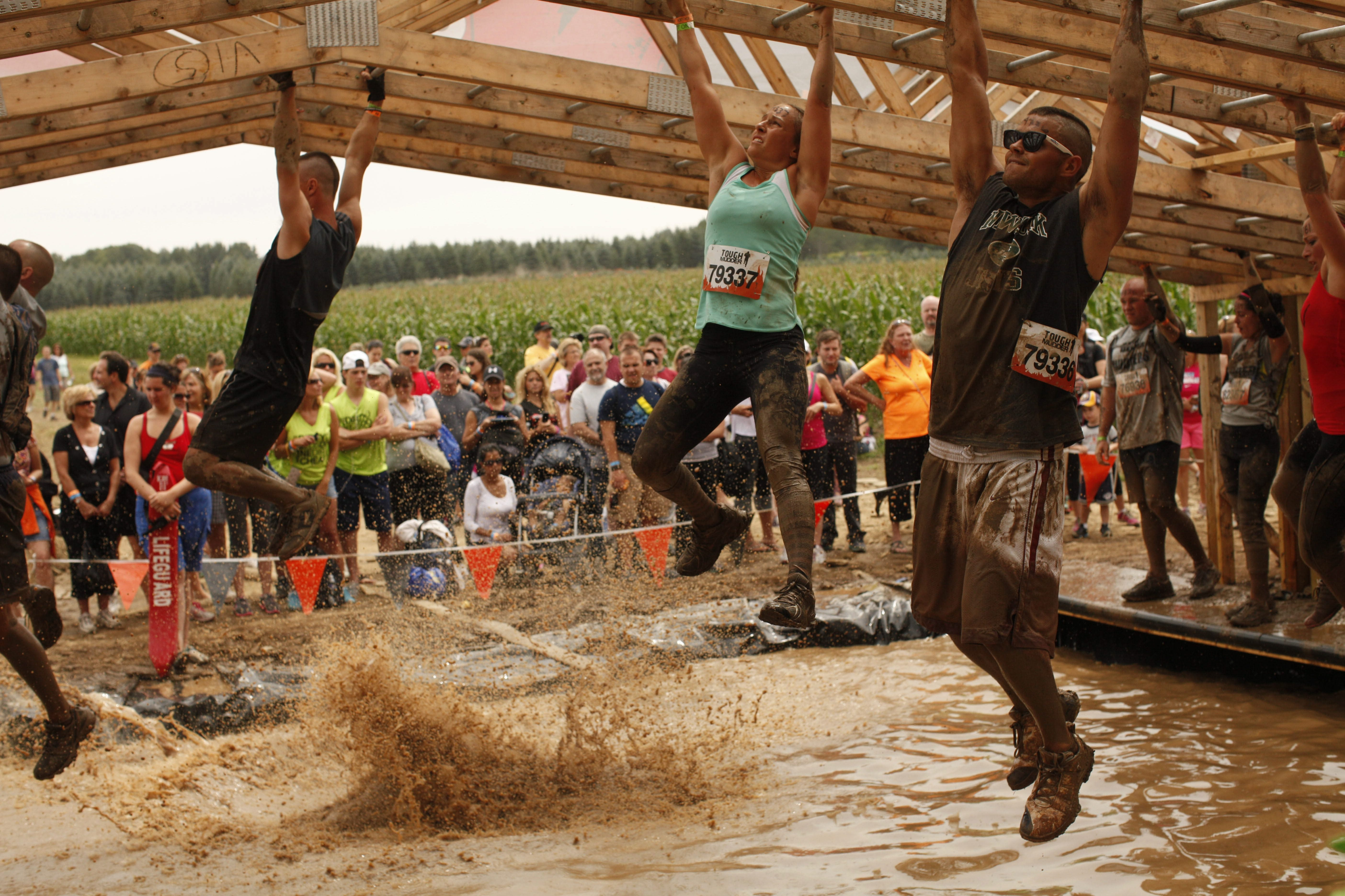 "Tough Mudder participants climb across the ""Funky Monkey"" obstacle – or fall into the pit of mud below – during the 12-mile obstacle course in Andover, Saturday.  The course was designed by Britsh Special Forces."