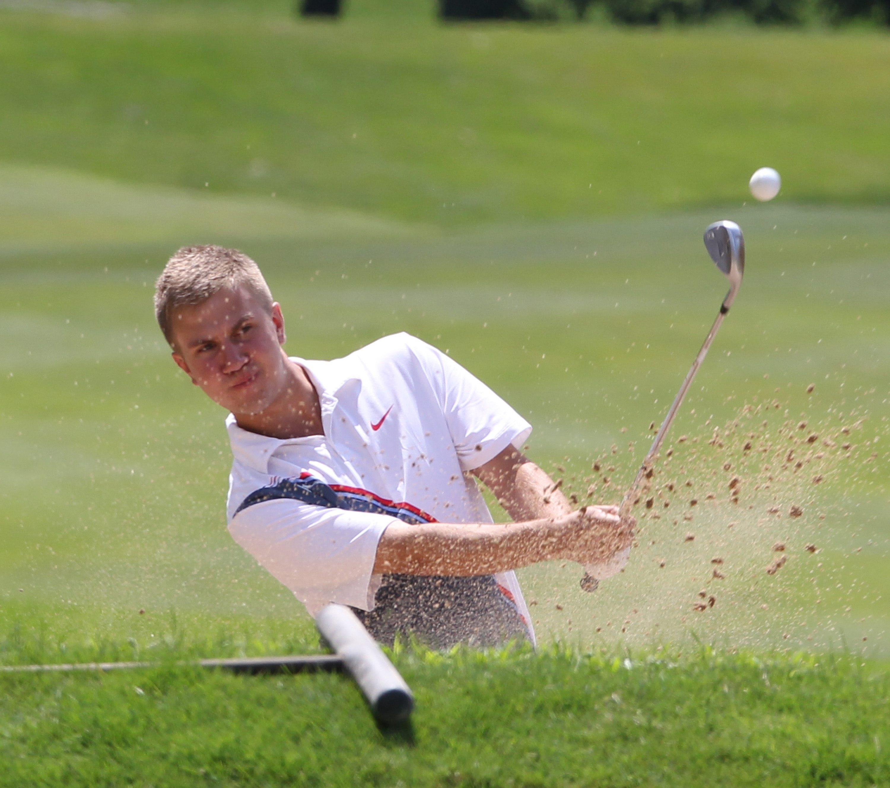 Lancaster's Austin Nowak hits out of the sand and onto the green on the 17th hole at Niagara Falls CC.