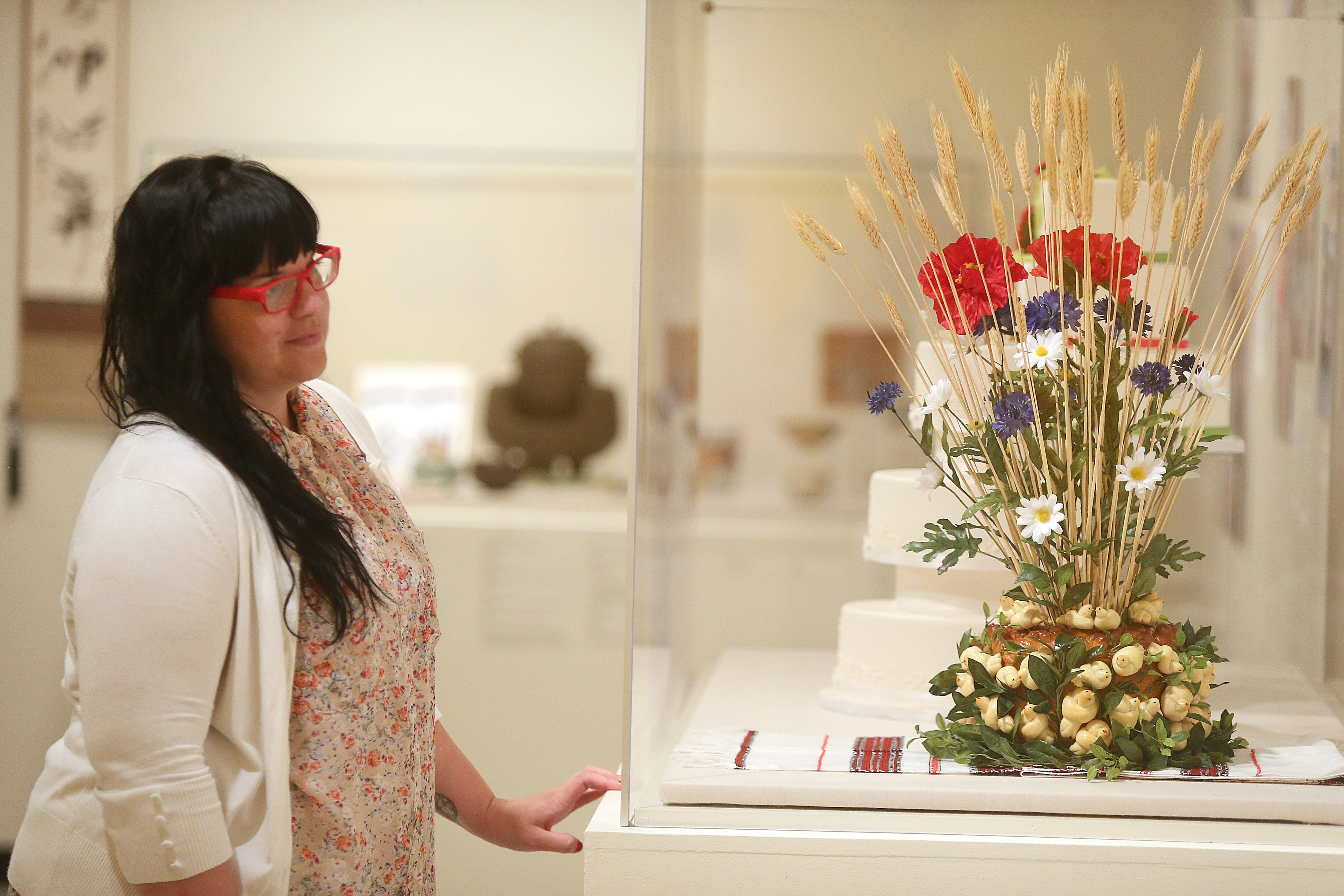 Hannah Cattarin of Buffalo looks at korovai, or Ukrainian wedding bread, in the new ethnic food exhibit at the Castellani Art Museum on July 23.